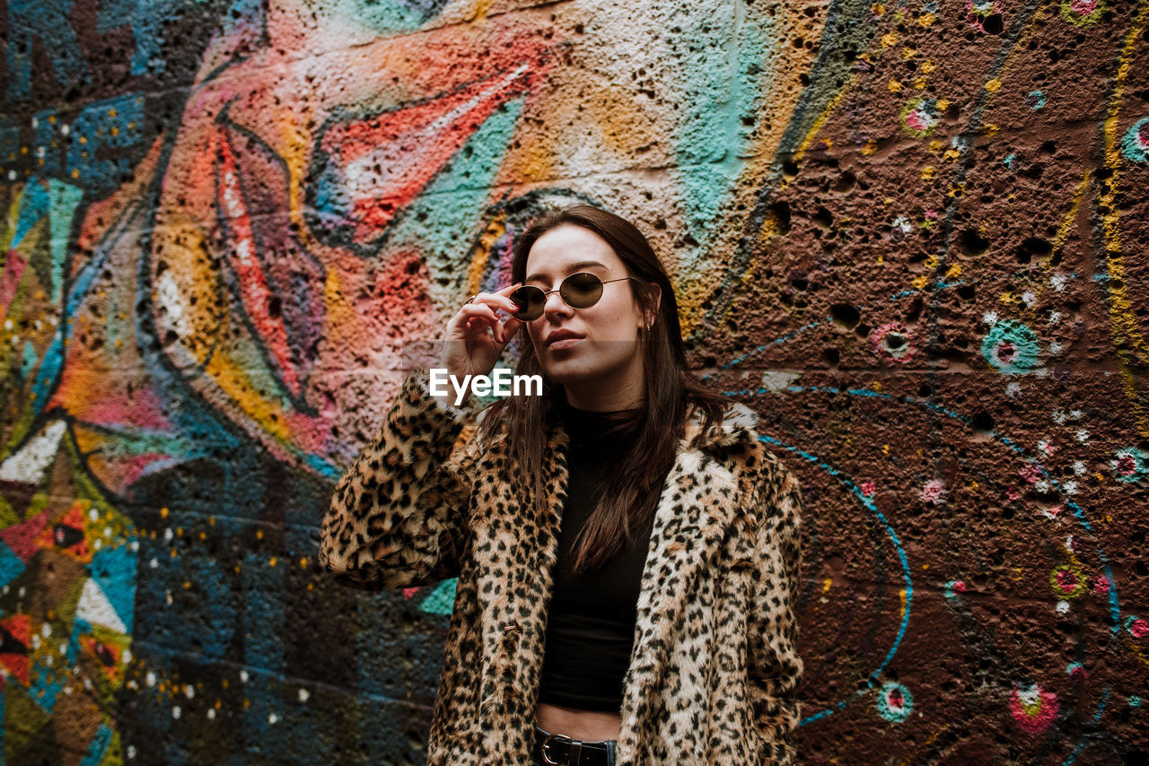 Young Woman In Sunglasses Standing Against Graffiti Wall