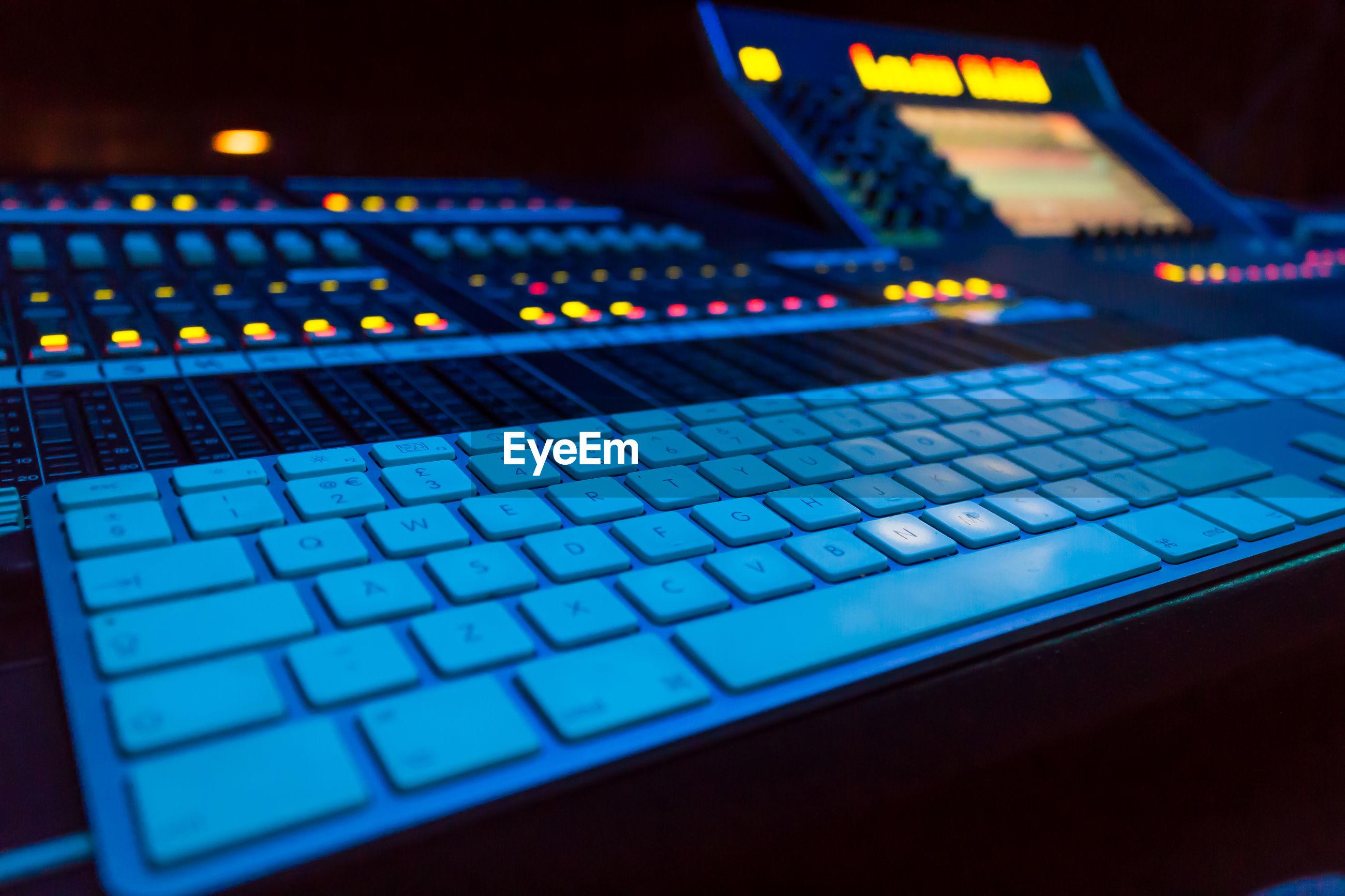 Close-up of computer keyboard by illuminated sound mixer
