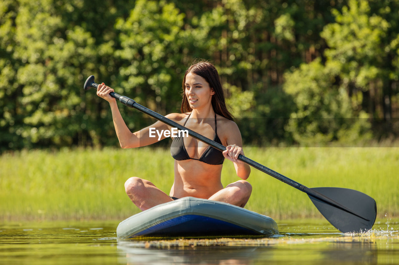 Young Woman Wearing Bikini While Paddleboarding In Lake
