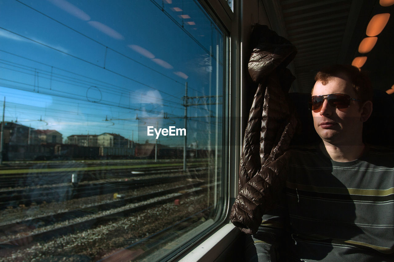 Middle aged man in googles travelling by train. public transport and transportation concept