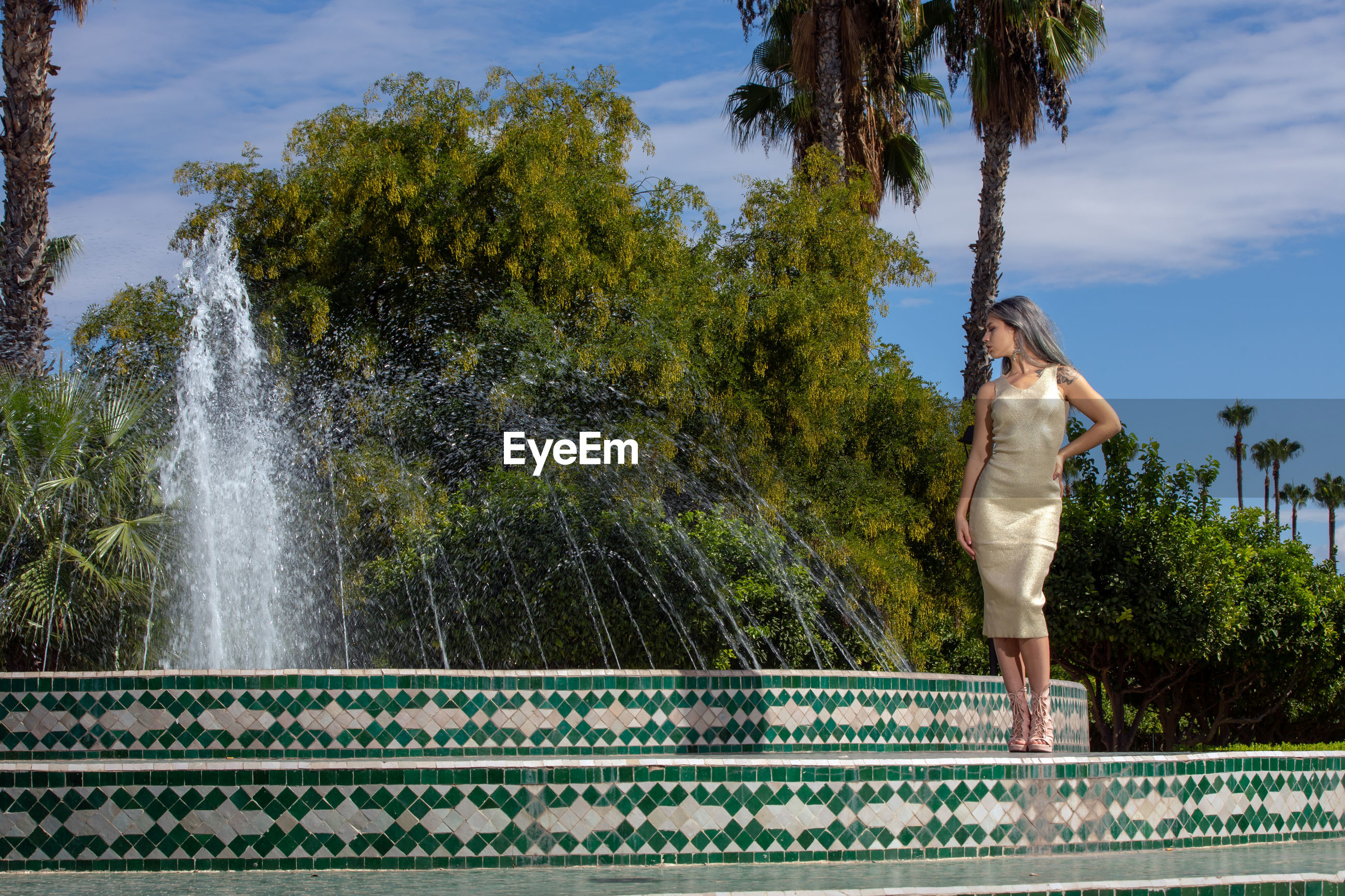 Woman standing by fountain against trees