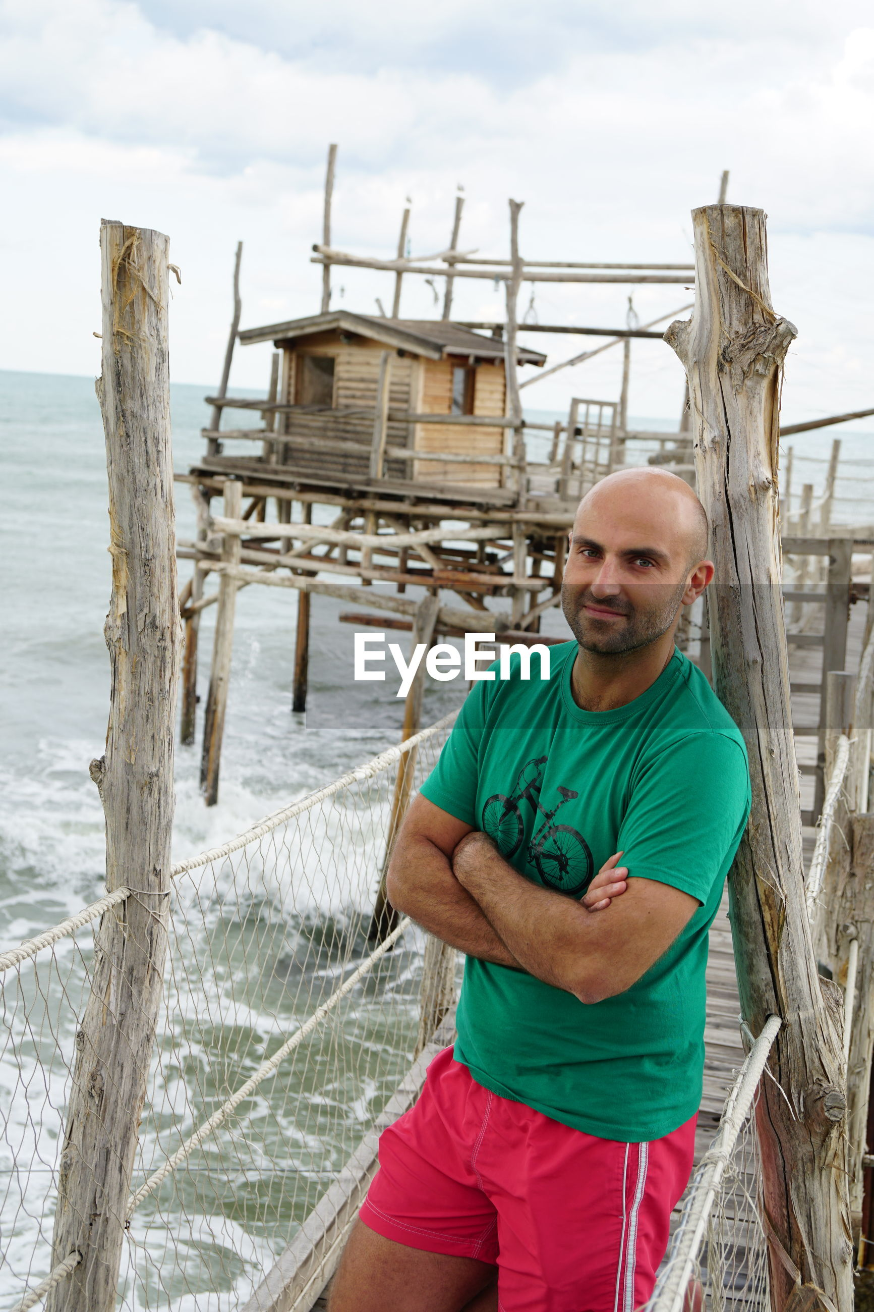 Portrait of bald man standing on pier over sea