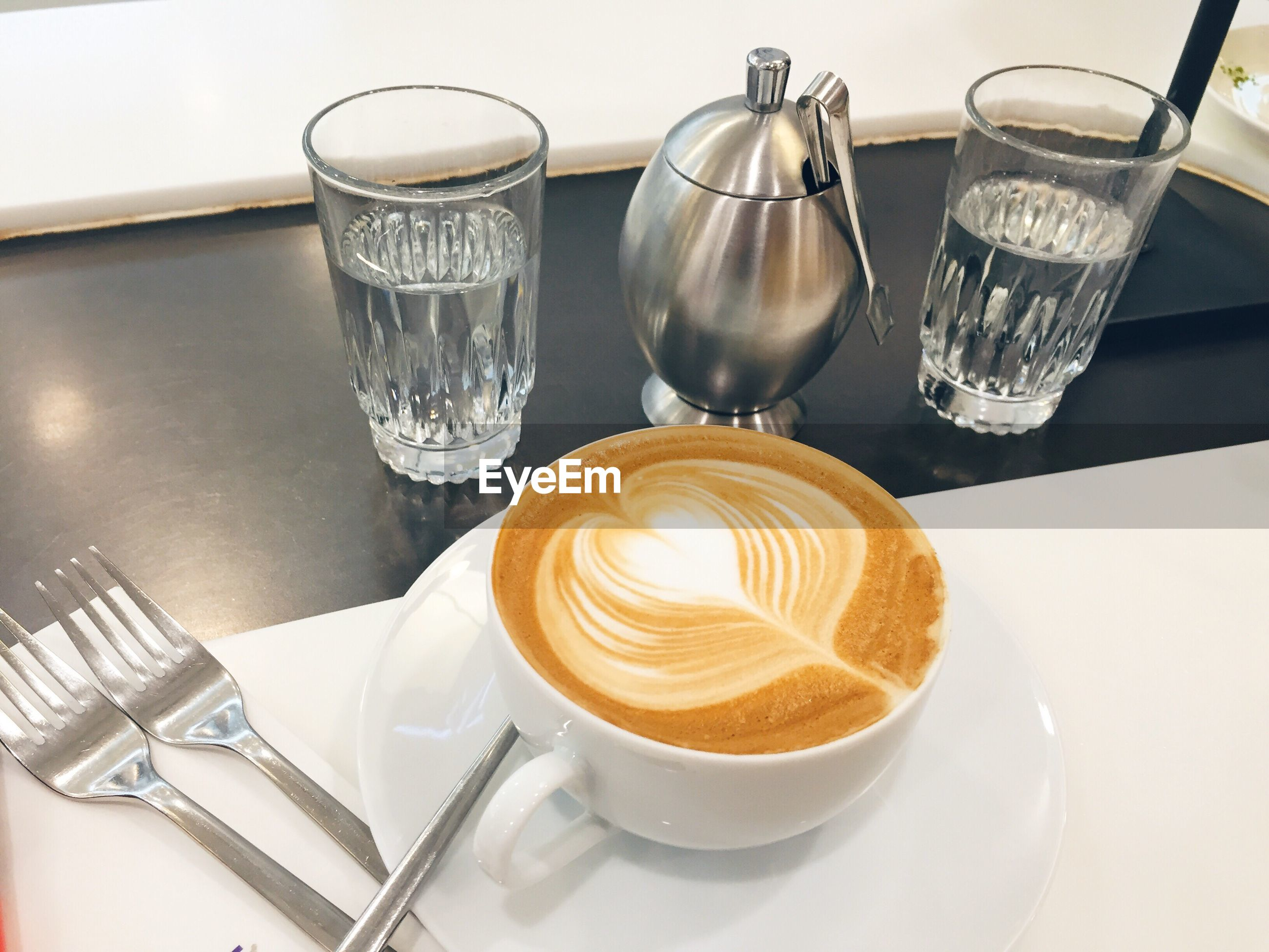 High angle view of coffee and drinking glasses on table