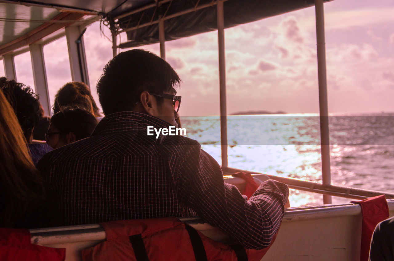 Rear View Of Man Sailing In Ferry Against Sky