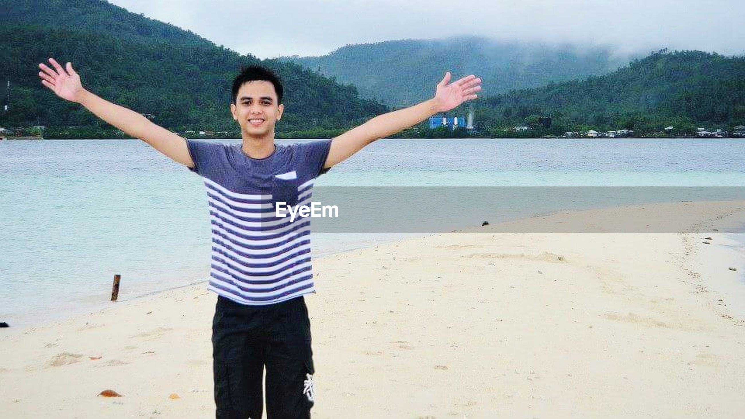 arms raised, human arm, happiness, smiling, one person, looking at camera, day, standing, outdoors, real people, casual clothing, water, young adult, enjoyment, portrait, human body part, nature, leisure activity, vacations, beach, young women, cheerful, beautiful woman, lifestyles, tree, one woman only, only women, beauty in nature, sky, adult, adults only, people