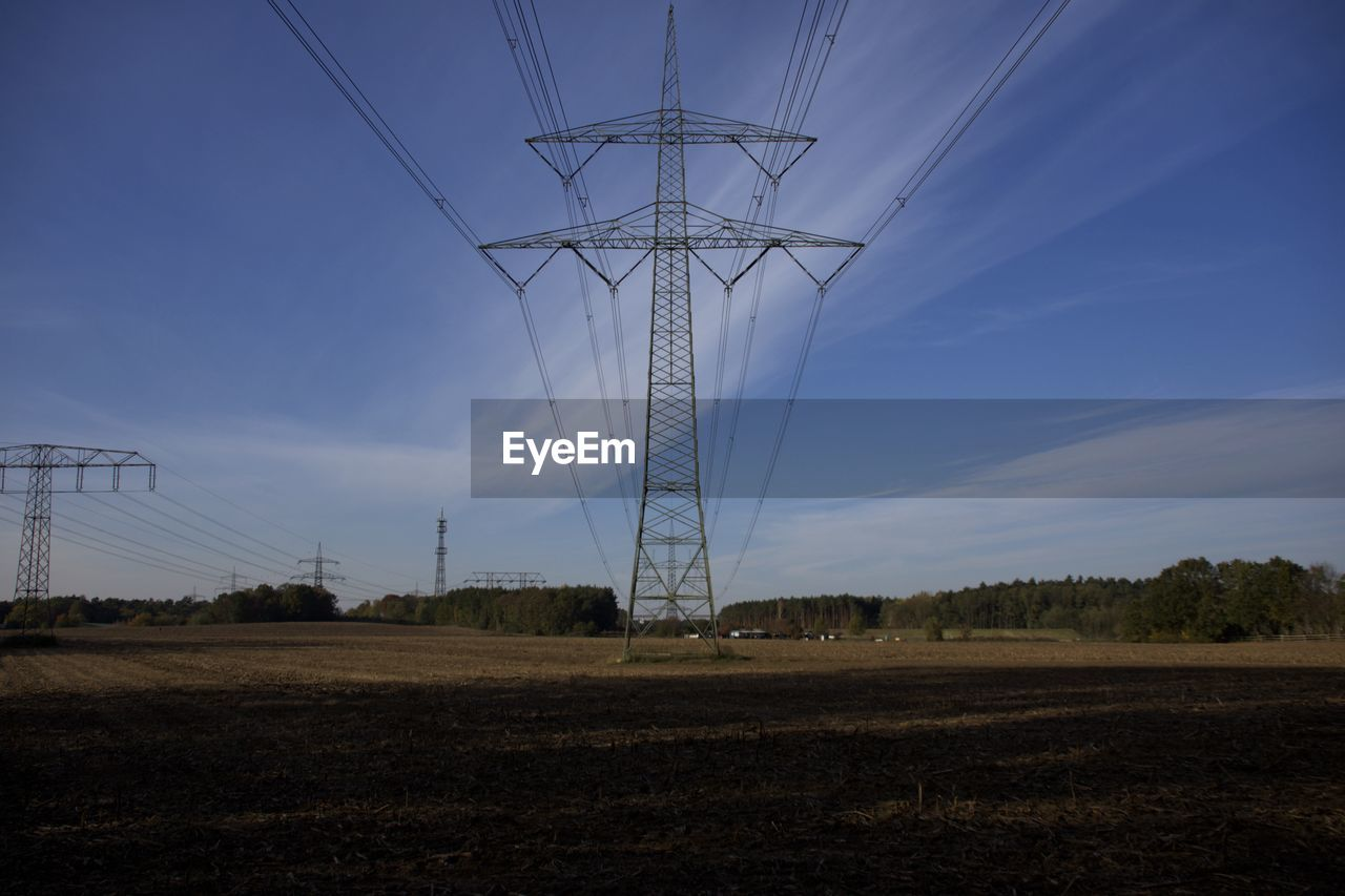 sky, fuel and power generation, electricity pylon, technology, landscape, electricity, power supply, nature, power line, land, connection, cable, field, environment, no people, outdoors, low angle view, agriculture, day, rural scene
