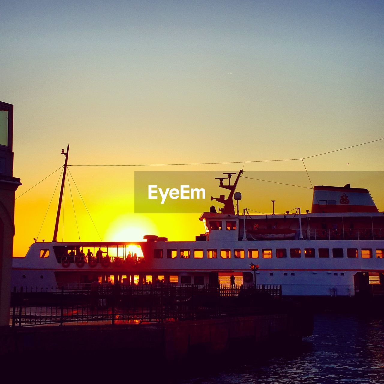 Ship moored at harbor against clear sky during sunset