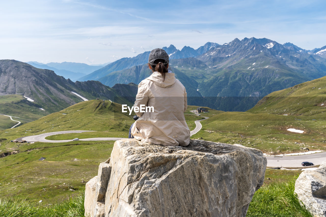Rear view of woman sitting against mountains on rock