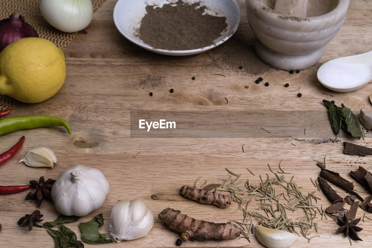garlic, ingredient, spice, preparation, food, high angle view, vegetable, cutting board, garlic bulb, indoors, food and drink, black peppercorn, healthy eating, table, freshness, kitchen, no people, ginger, day