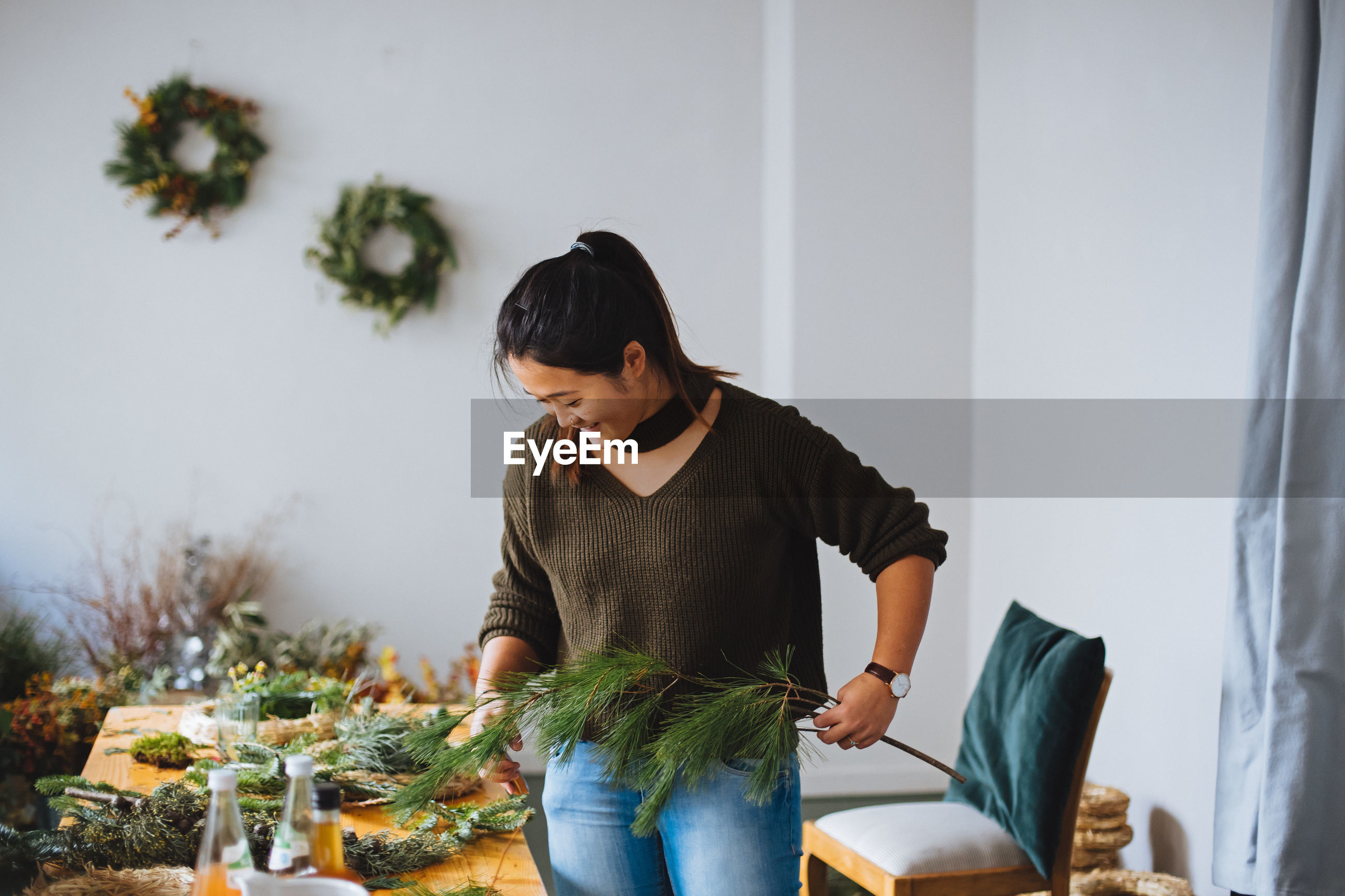 Young woman holding plant decorations at home during christmas