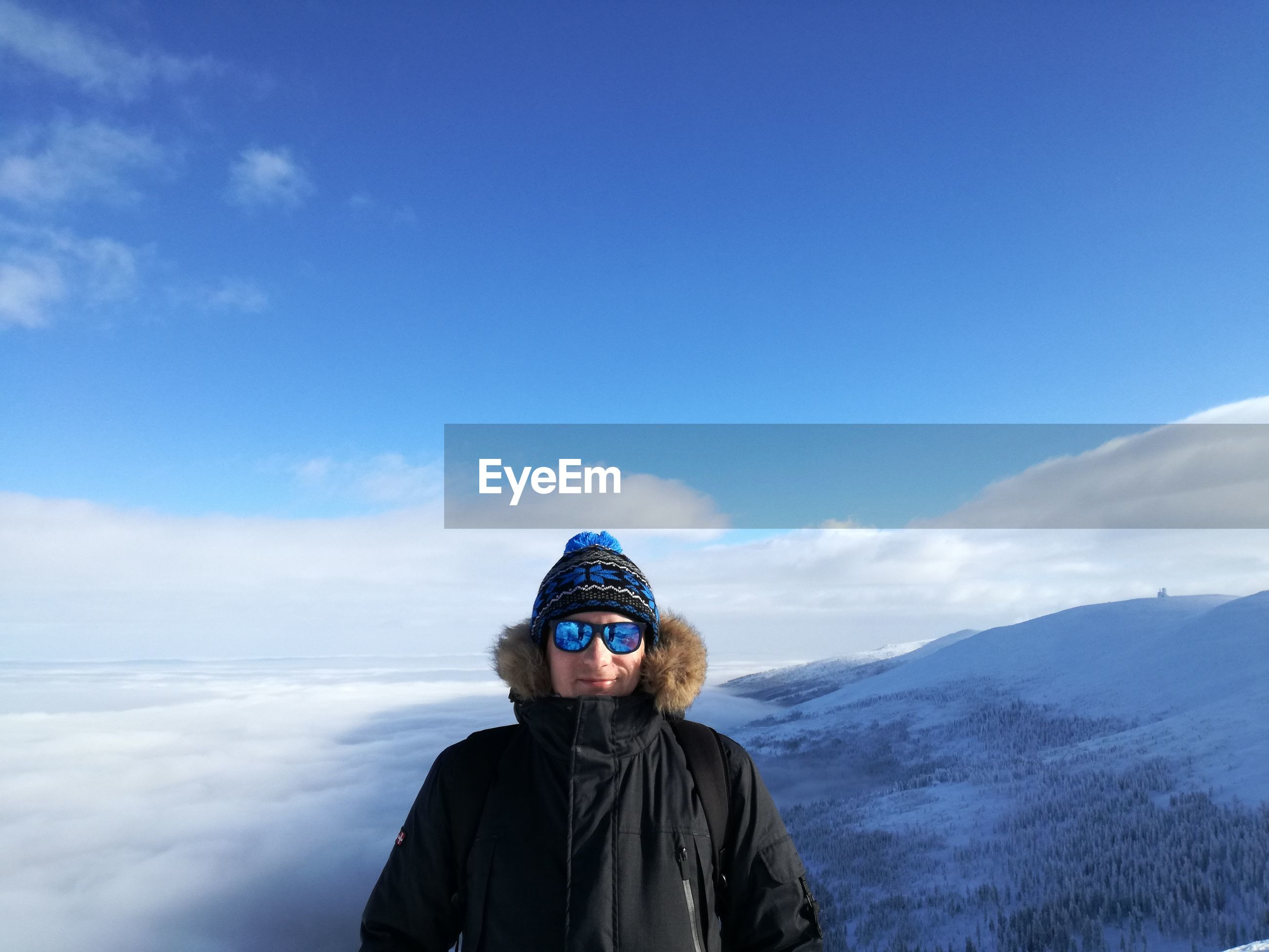 Portrait of man standing on snow covered mountain against sky