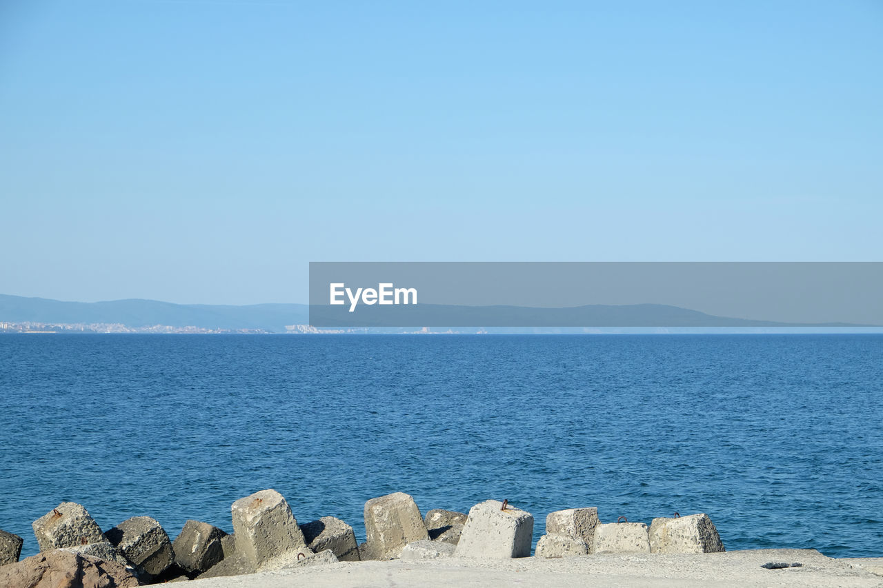 water, sea, sky, scenics - nature, beauty in nature, tranquility, tranquil scene, copy space, clear sky, day, idyllic, blue, nature, no people, mountain, non-urban scene, beach, remote, rock, outdoors, groyne