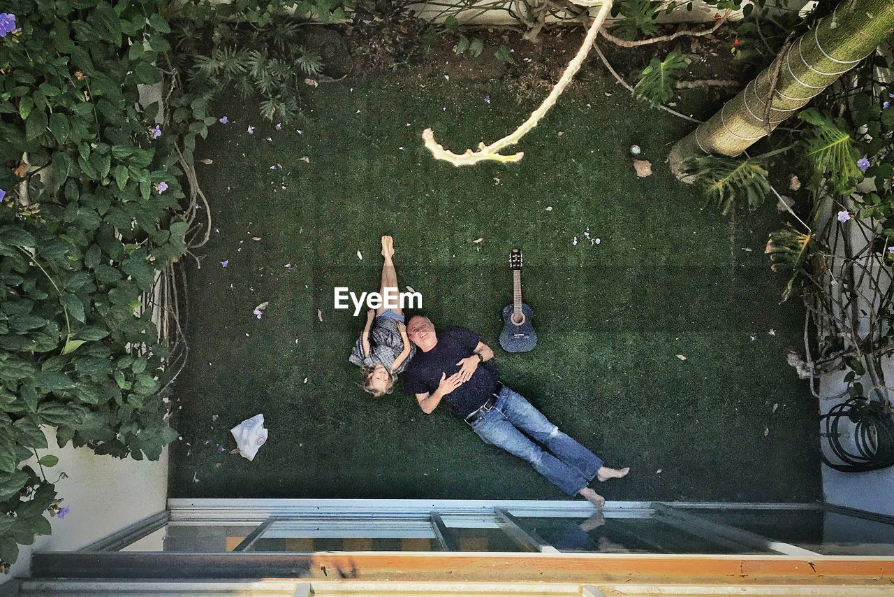 Directly Above Shot Of Grandfather Relaxing With Granddaughter At Yard