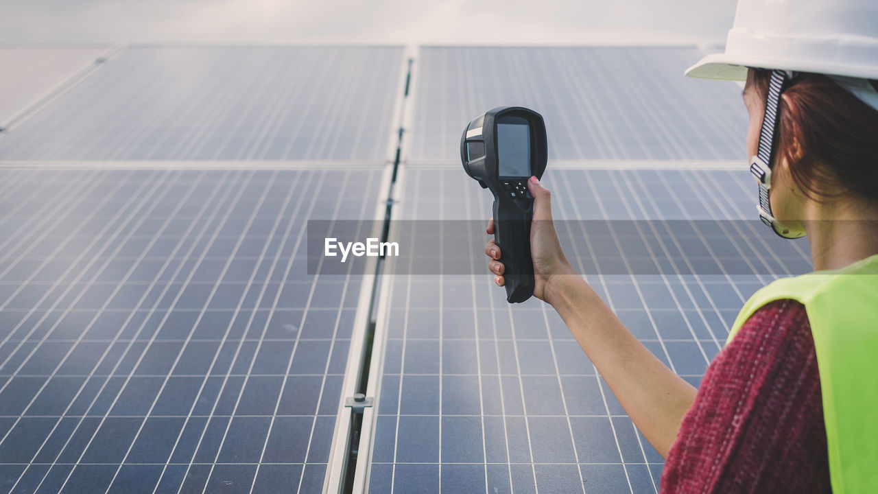 technology, environmental conservation, solar panel, solar energy, real people, renewable energy, occupation, alternative energy, fuel and power generation, nature, one person, environment, adult, headshot, holding, lifestyles, women, sky, environmental issues, electricity, sustainable resources, power supply