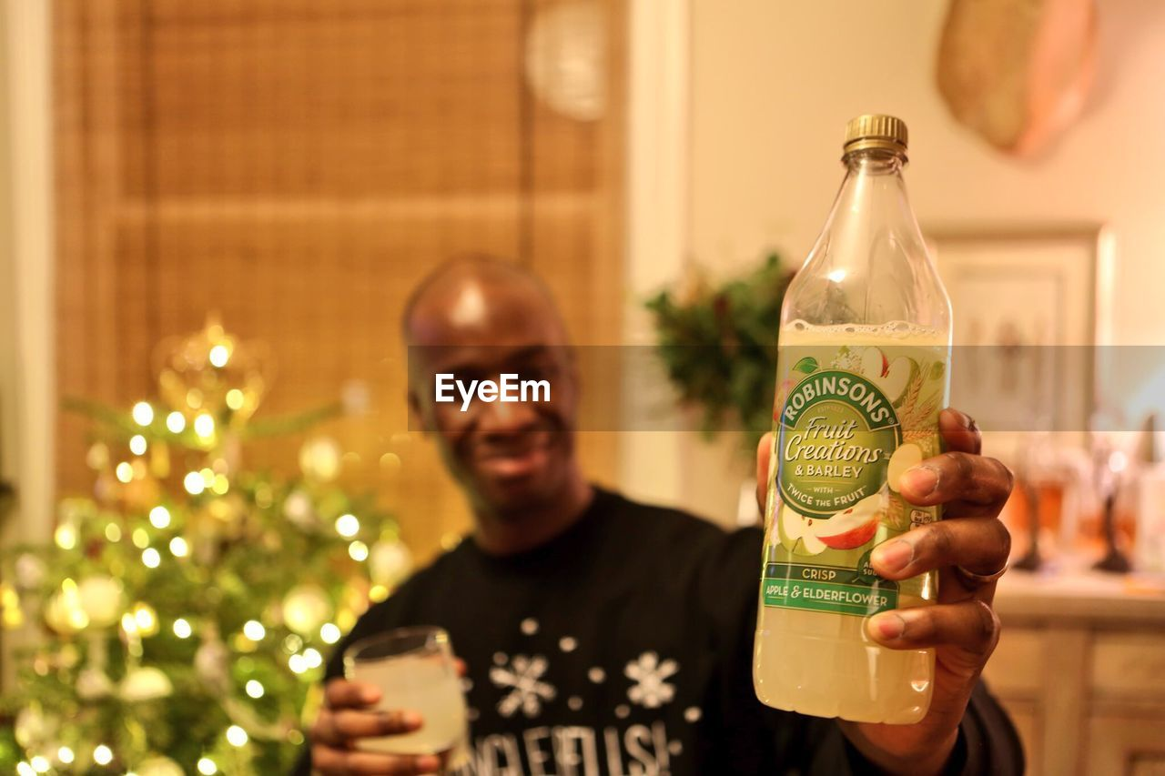 bottle, food and drink, one person, drink, indoors, real people, focus on foreground, front view, alcohol, refreshment, holiday - event, celebration, looking at camera, portrait, lifestyles, holding, christmas, men, smiling, close-up, day, one man only, young adult, freshness, adult, people