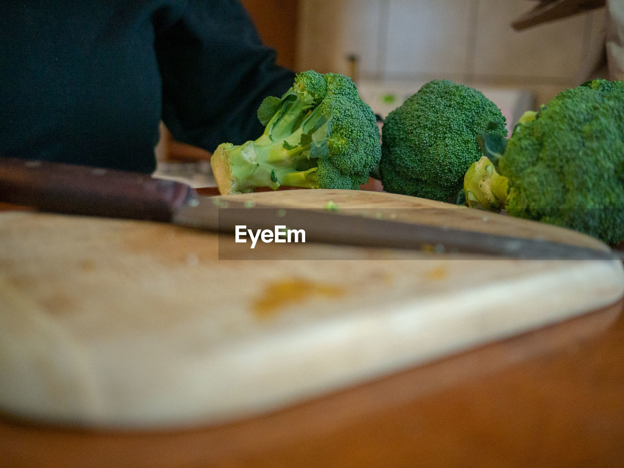 food and drink, food, healthy eating, indoors, selective focus, freshness, kitchen, one person, real people, vegetable, cutting board, domestic room, wellbeing, kitchen knife, close-up, green color, domestic kitchen, table, home, preparation, preparing food, hand