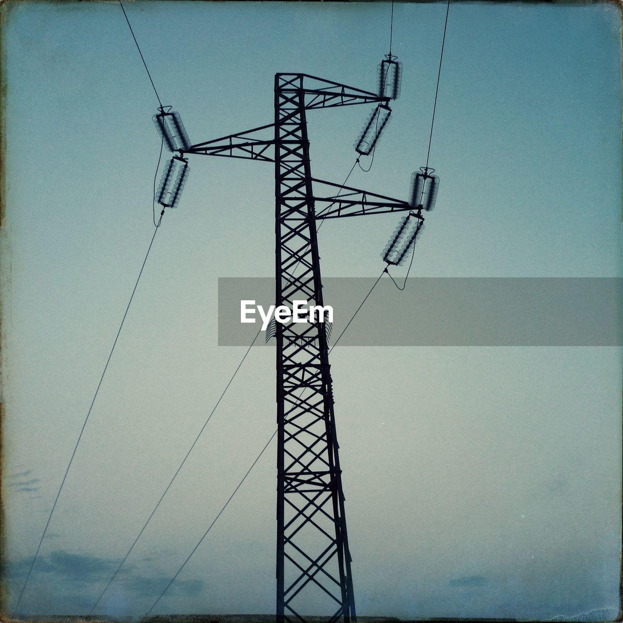Silhouette electricity pylon at dusk