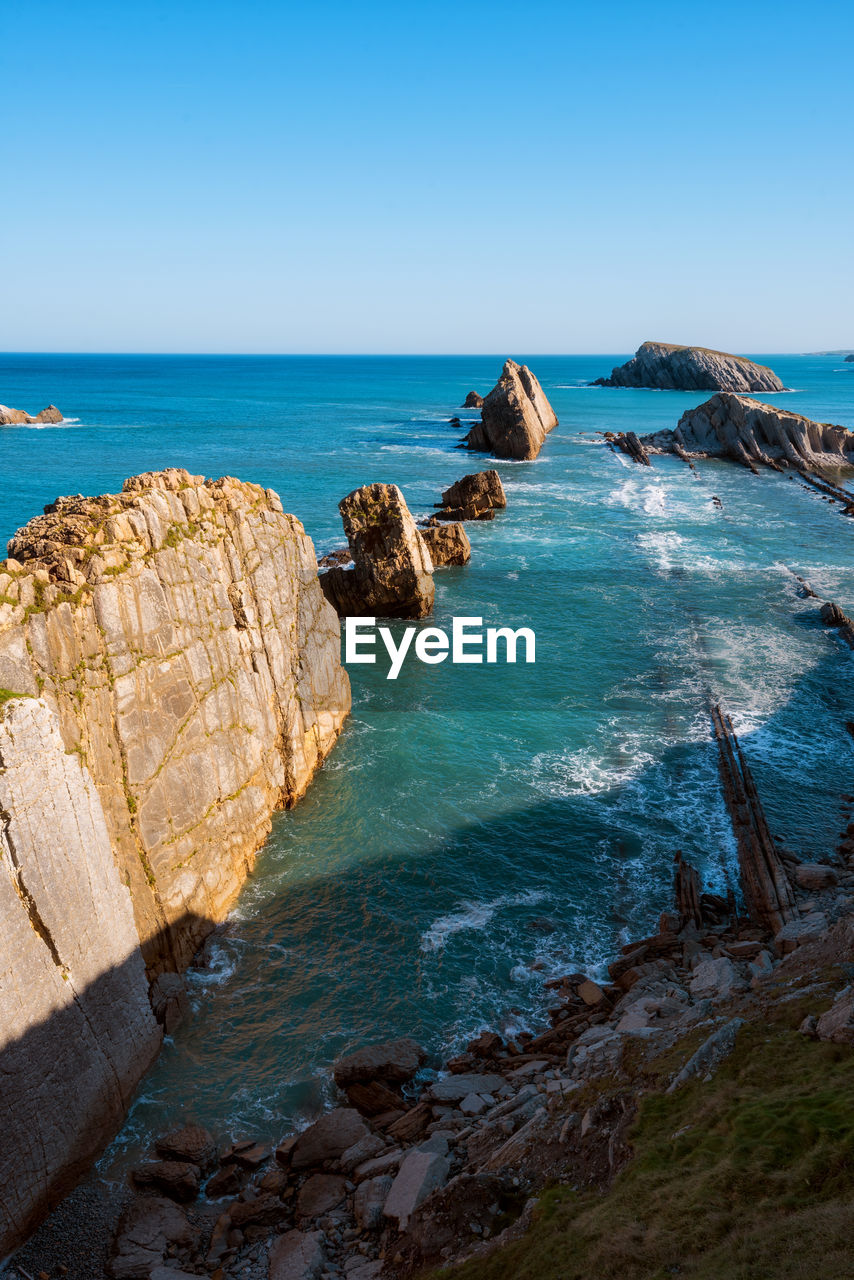 sea, water, sky, rock, beauty in nature, rock - object, horizon, scenics - nature, horizon over water, solid, blue, tranquil scene, land, beach, rock formation, nature, tranquility, clear sky, no people, outdoors, rocky coastline