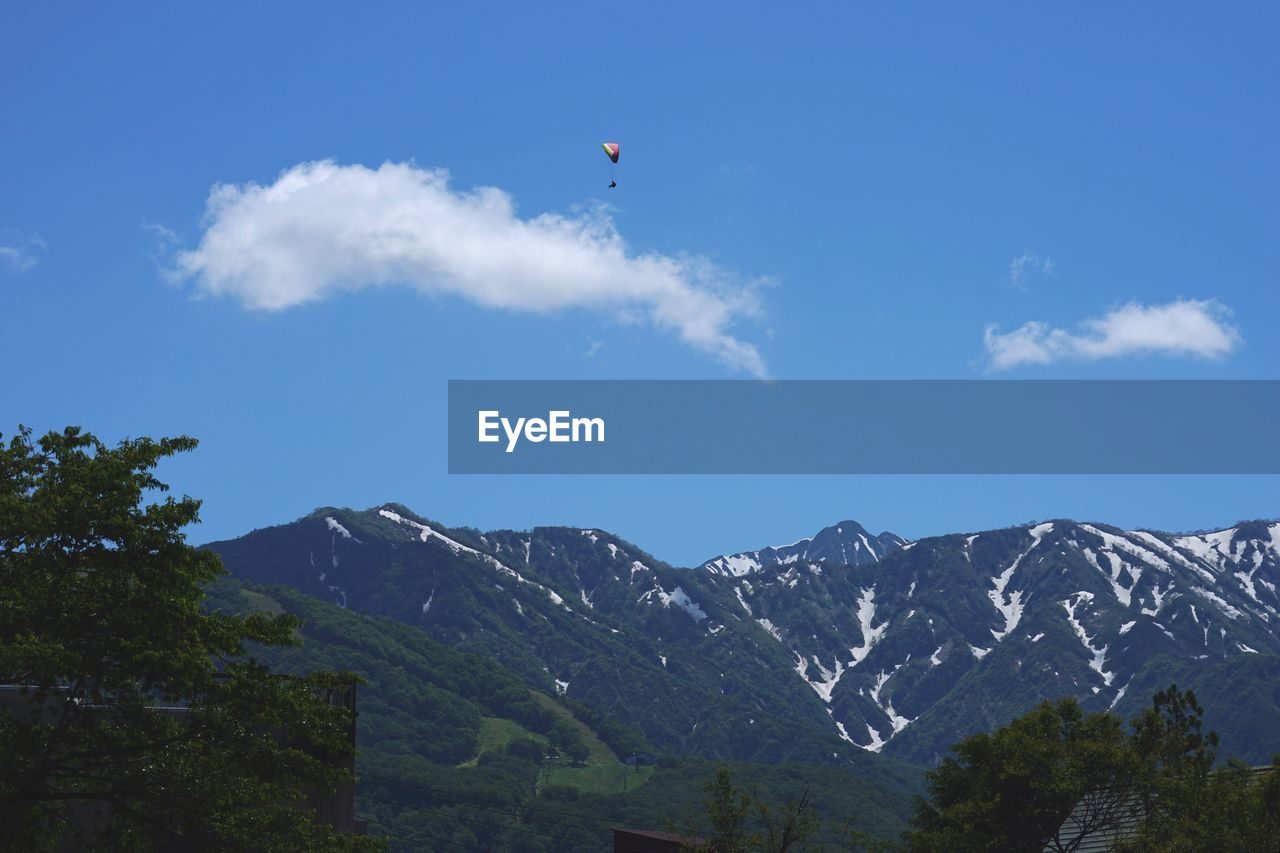 mountain, sky, scenics - nature, beauty in nature, mountain range, tranquil scene, cloud - sky, tranquility, flying, low angle view, nature, day, non-urban scene, mid-air, paragliding, outdoors, tree, adventure, environment, snow, no people, mountain peak, snowcapped mountain