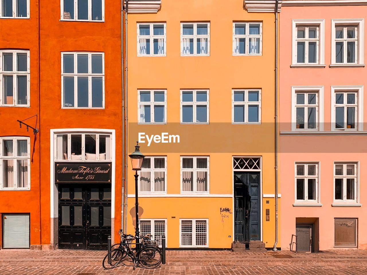 architecture, building exterior, window, built structure, bicycle, building, city, residential district, transportation, orange color, day, sunlight, house, outdoors, mode of transportation, no people, city life, street, land vehicle, multi colored, row house, apartment