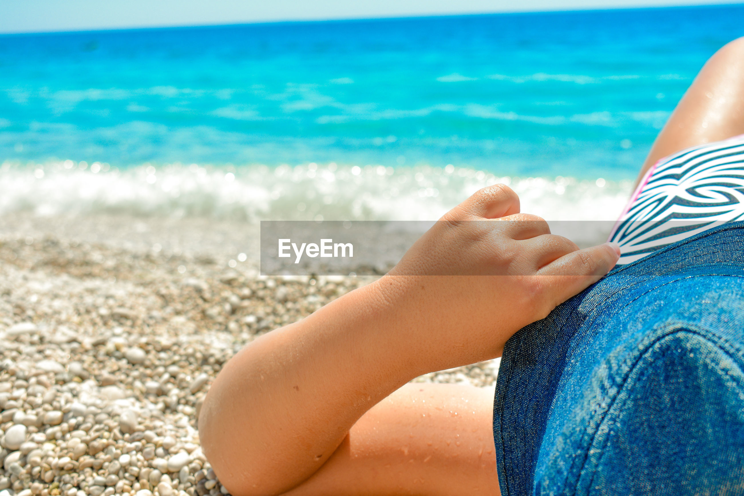 Girl wearing hat lying at beach during sunny day