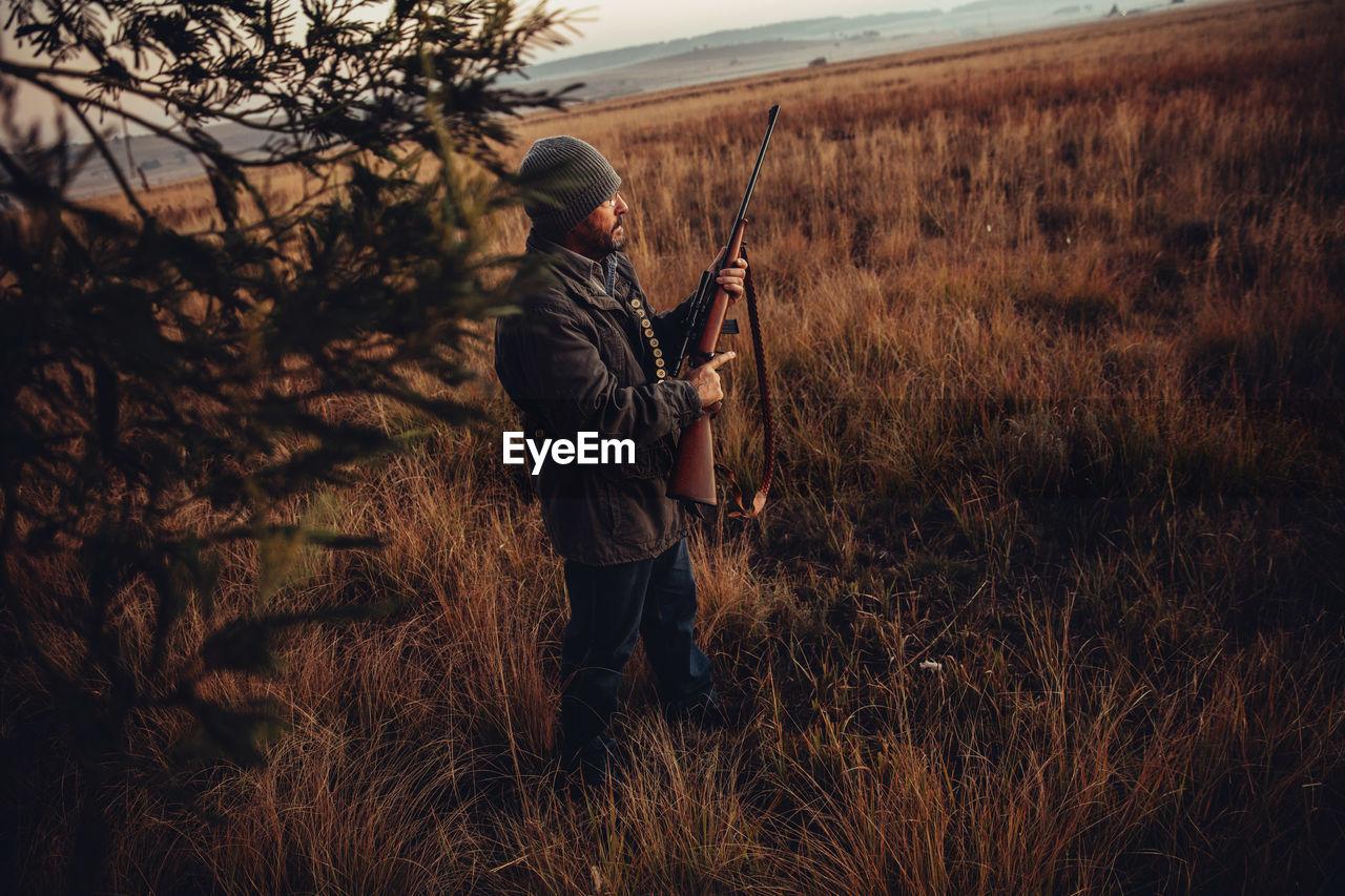 Hunter With Shotgun Standing In Field