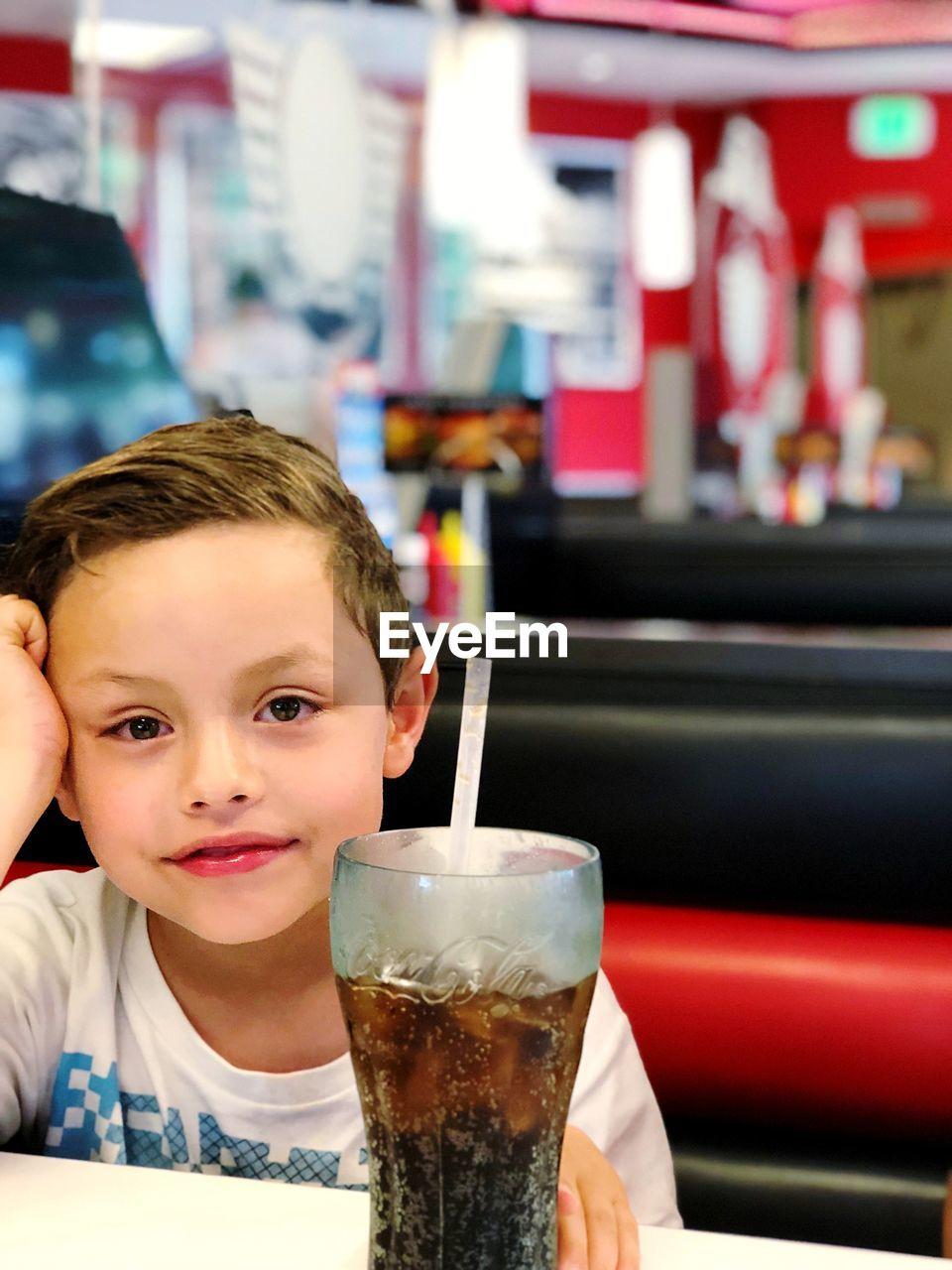 PORTRAIT OF BOY DRINKING GLASS IN RESTAURANT