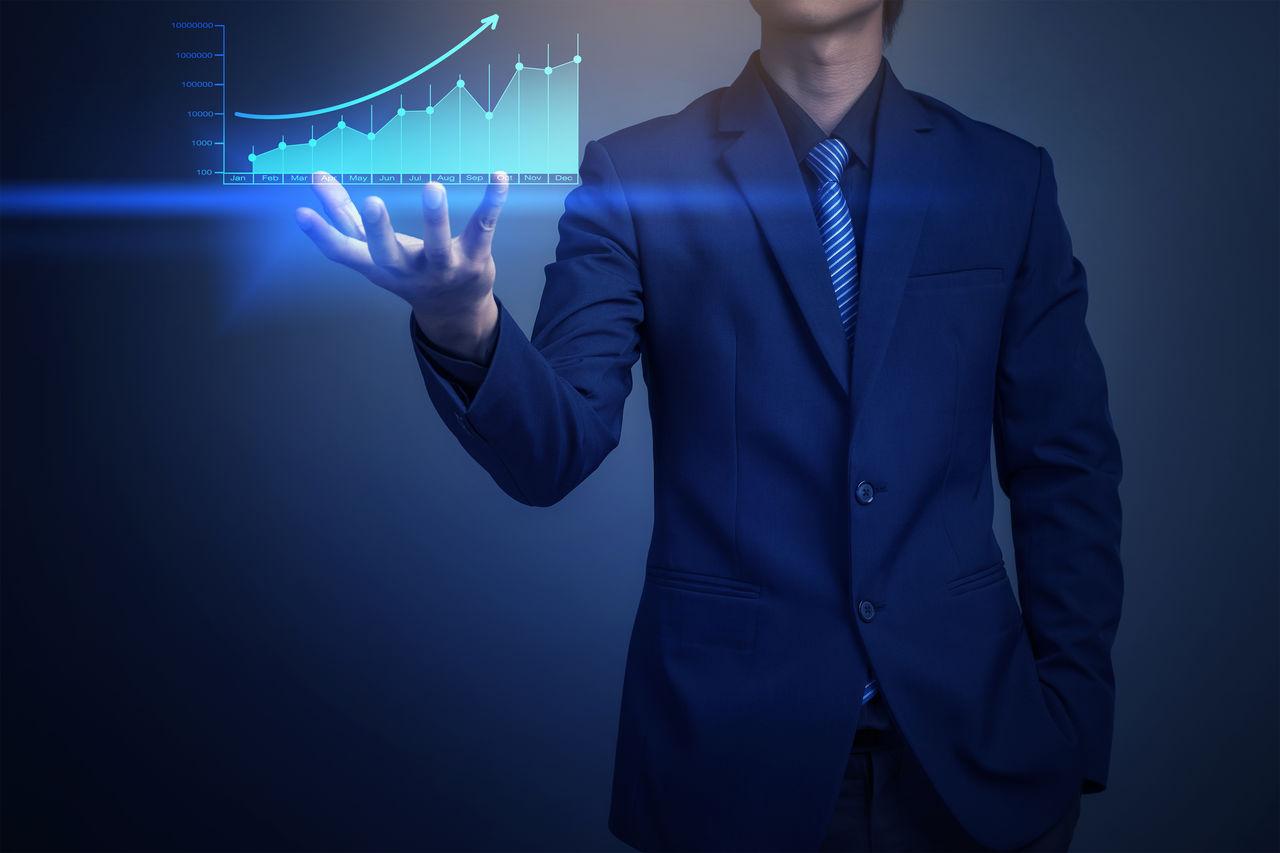 Digital composite image of businessman holding graph against blue background