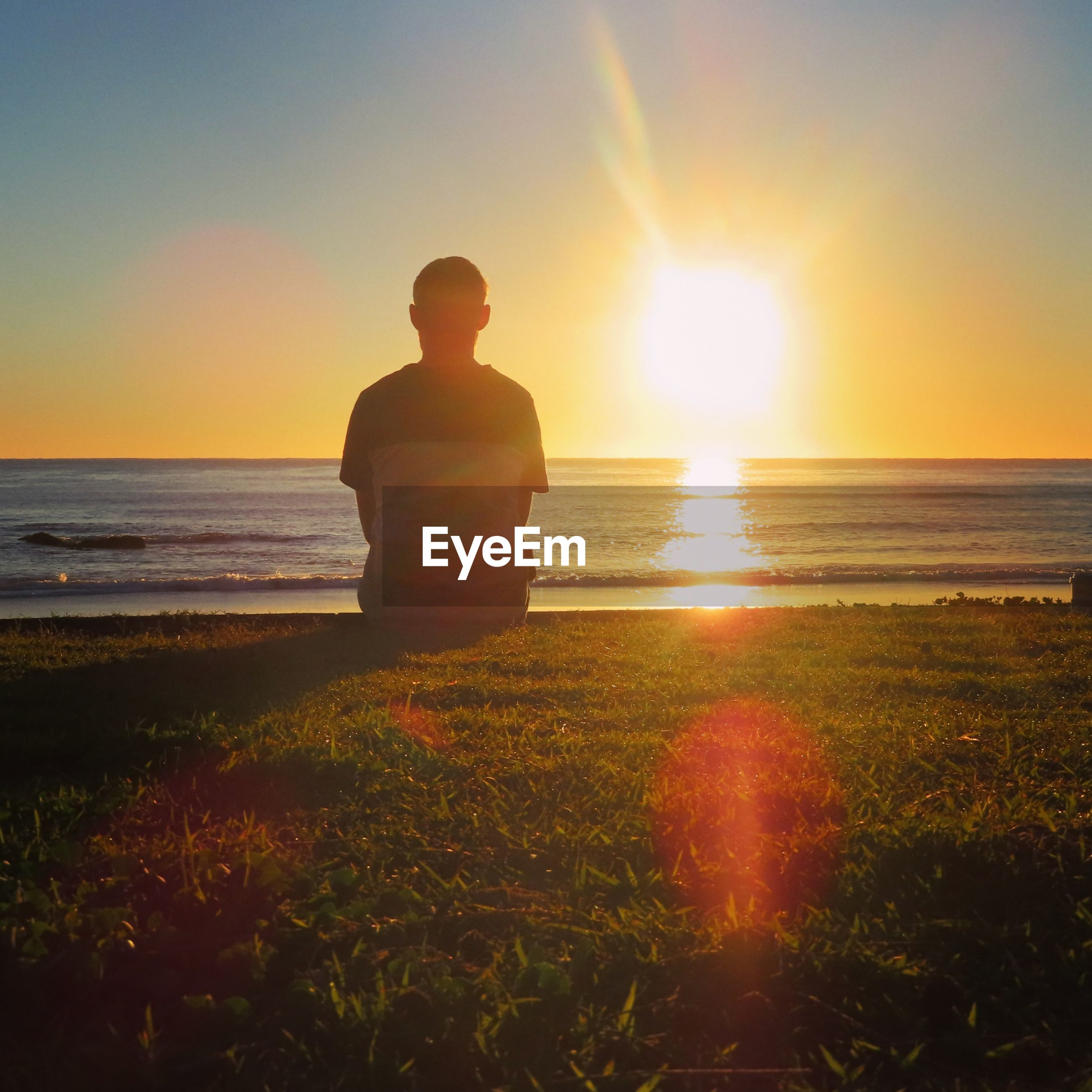 Rear view of man looking at sea during sunset