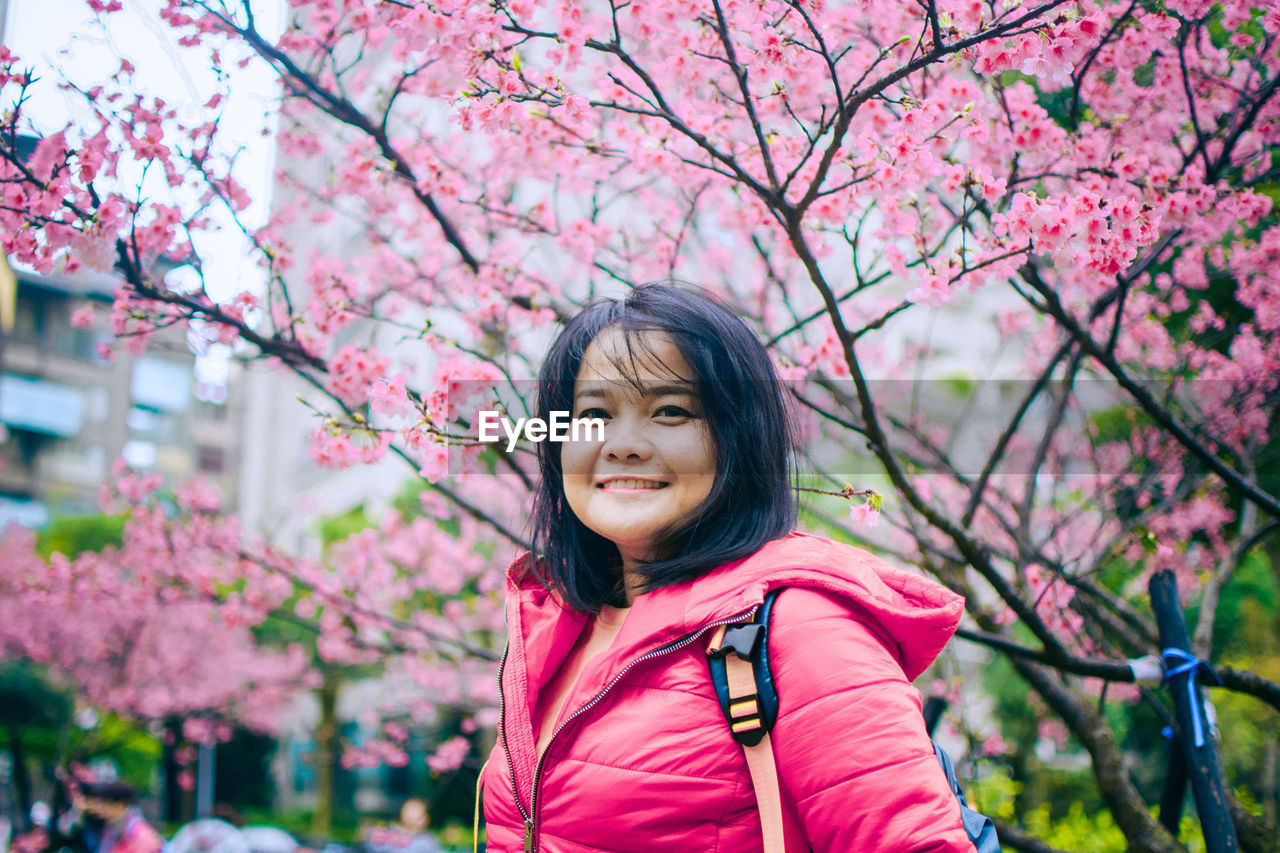 plant, pink color, real people, portrait, one person, flower, flowering plant, tree, looking at camera, women, growth, beauty in nature, leisure activity, lifestyles, nature, springtime, smiling, front view, focus on foreground, cherry blossom, outdoors, cherry tree, hairstyle