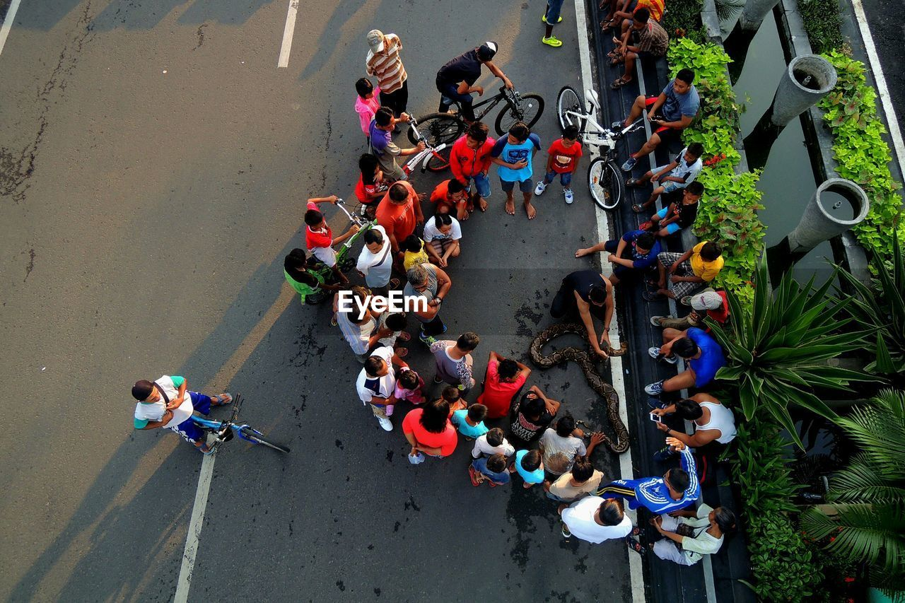 Snake charmer amidst people sitting on street