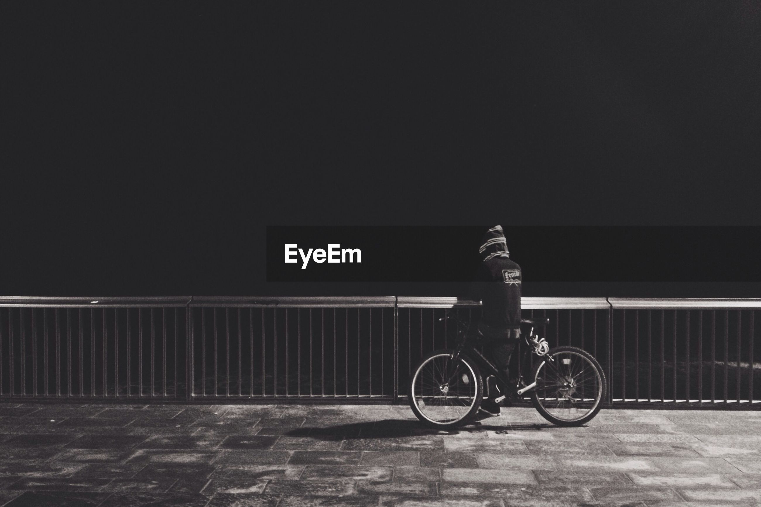 Person standing with bicycle at railing against sea at night