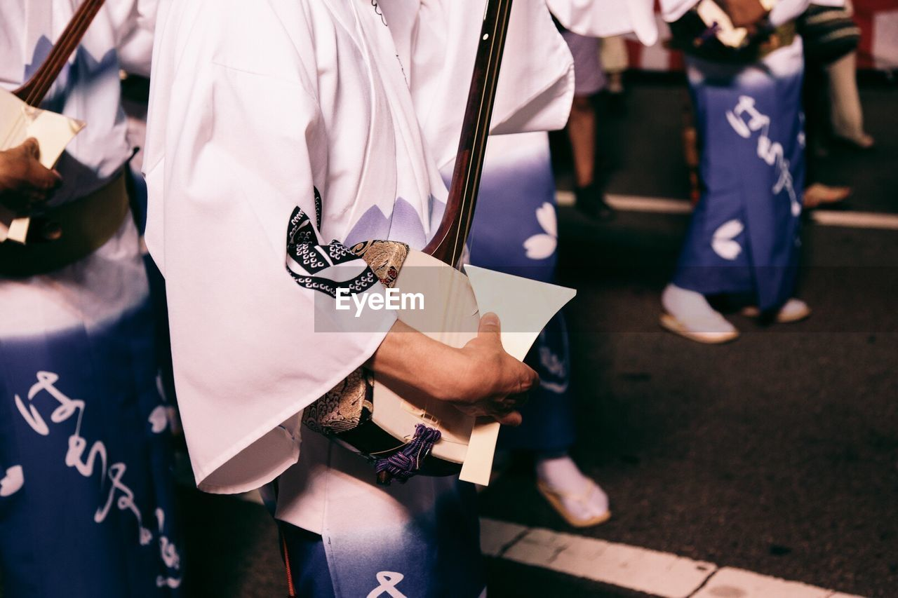 Midsection Of Artists Playing Shamisen On Street During Awa Odori