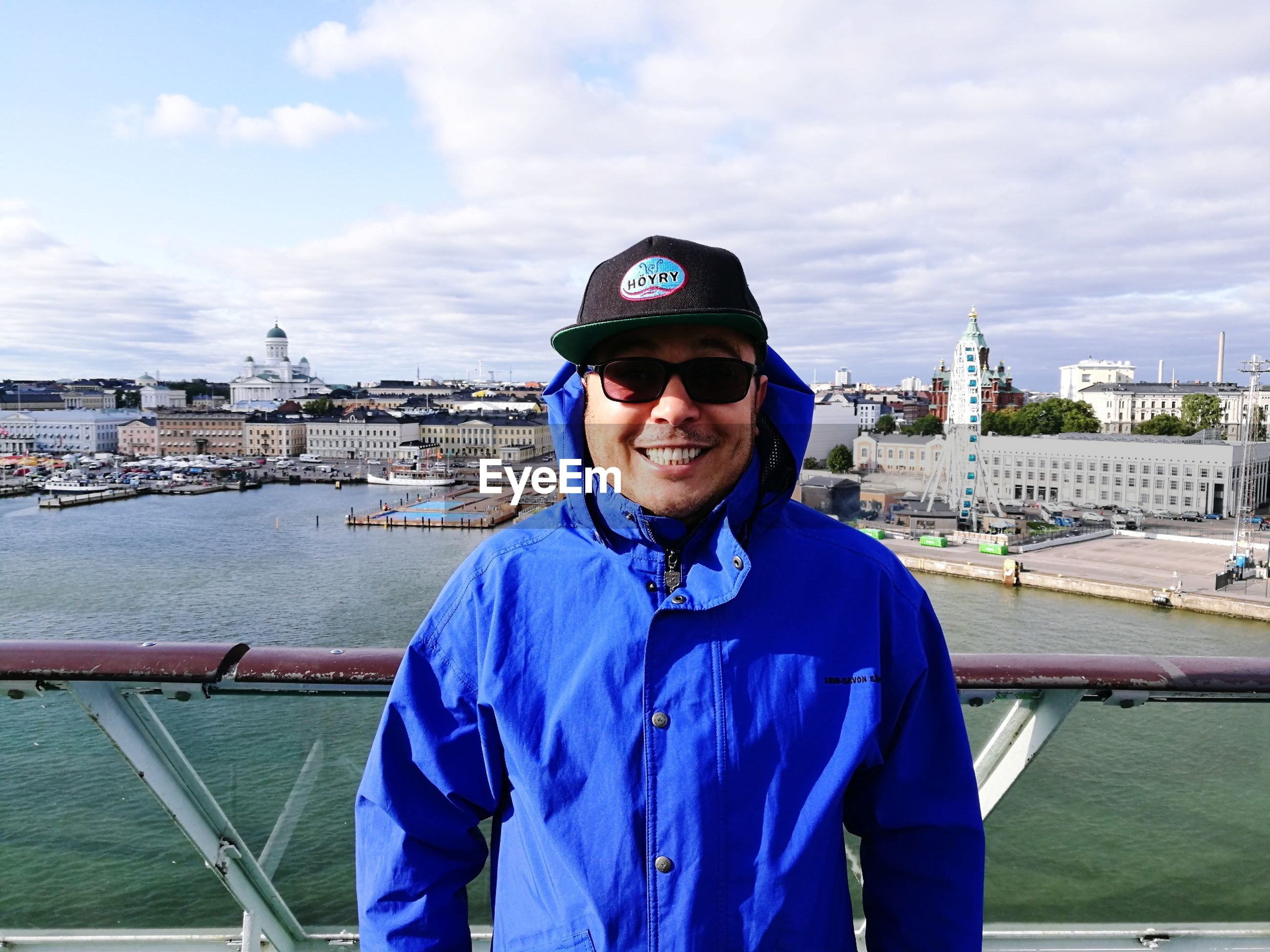 Portrait of smiling man standing against cityscape and cloudy sky
