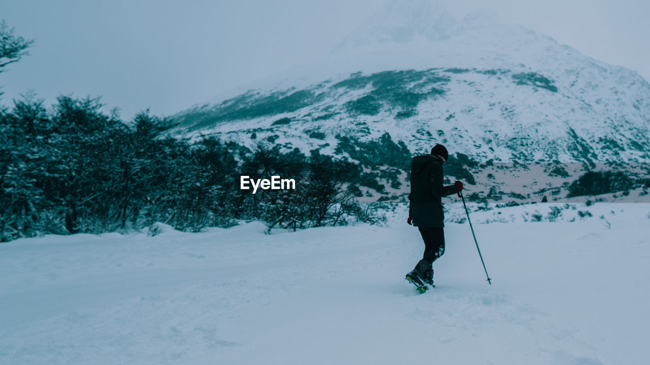 FULL LENGTH OF PERSON SKIING ON SNOWCAPPED FIELD AGAINST MOUNTAIN