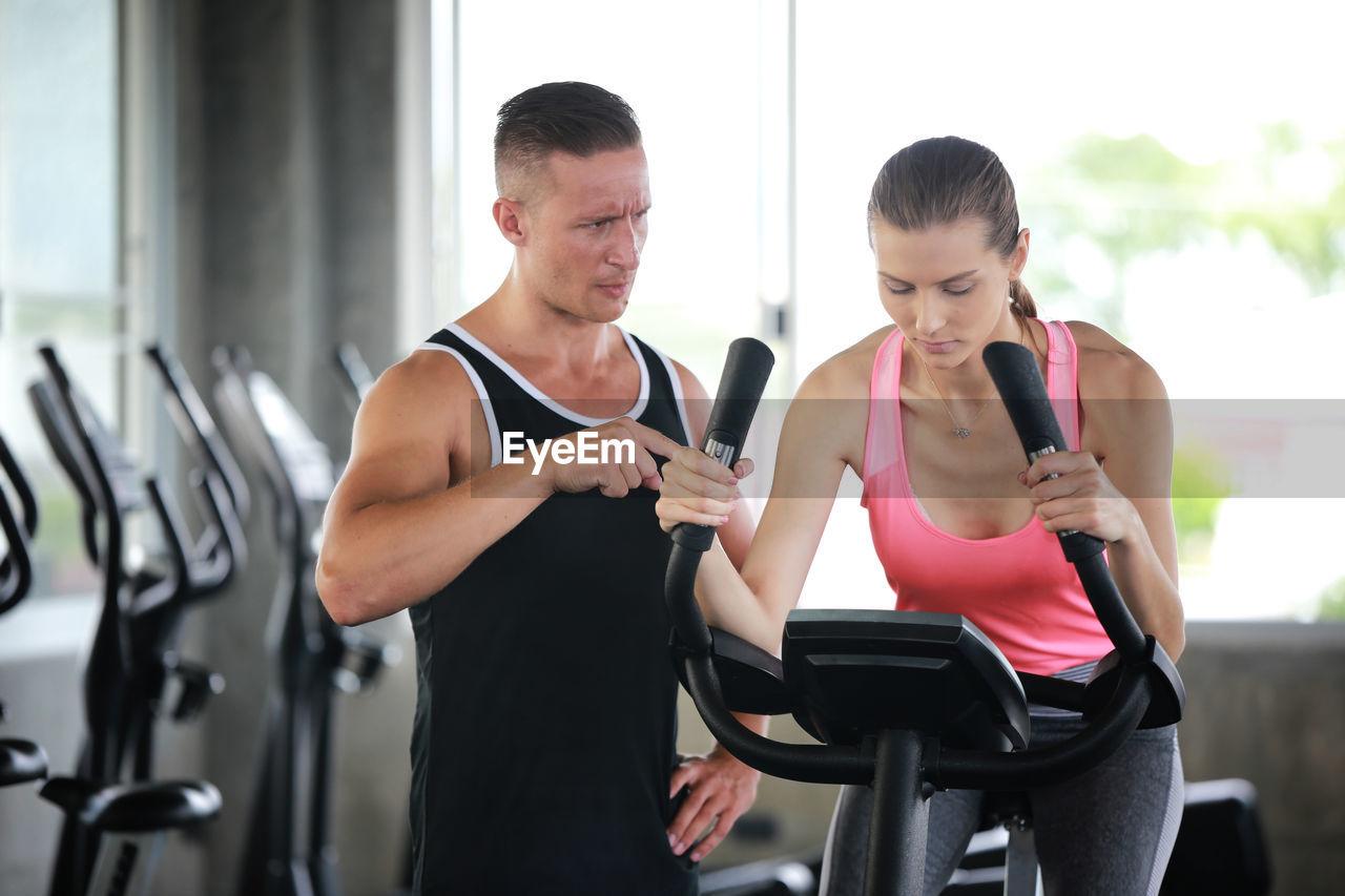 Man Guiding Friend In Gym