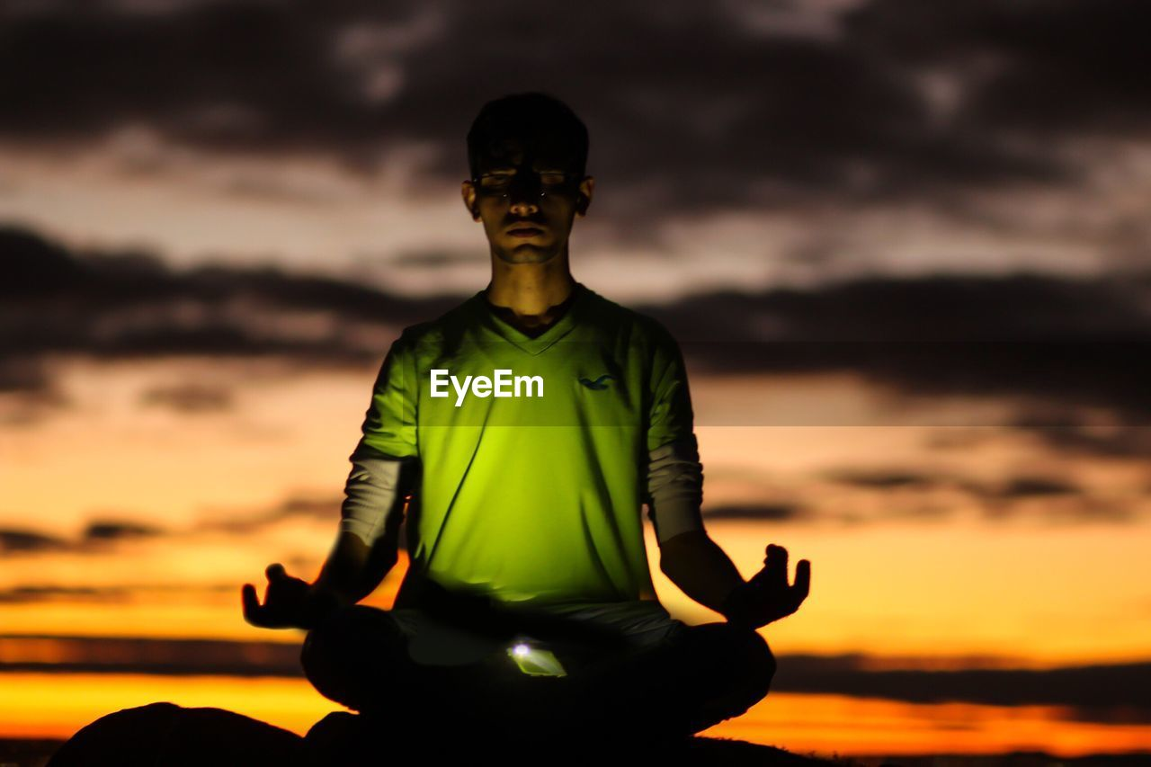 Young man performing yoga while sitting against sky during sunset