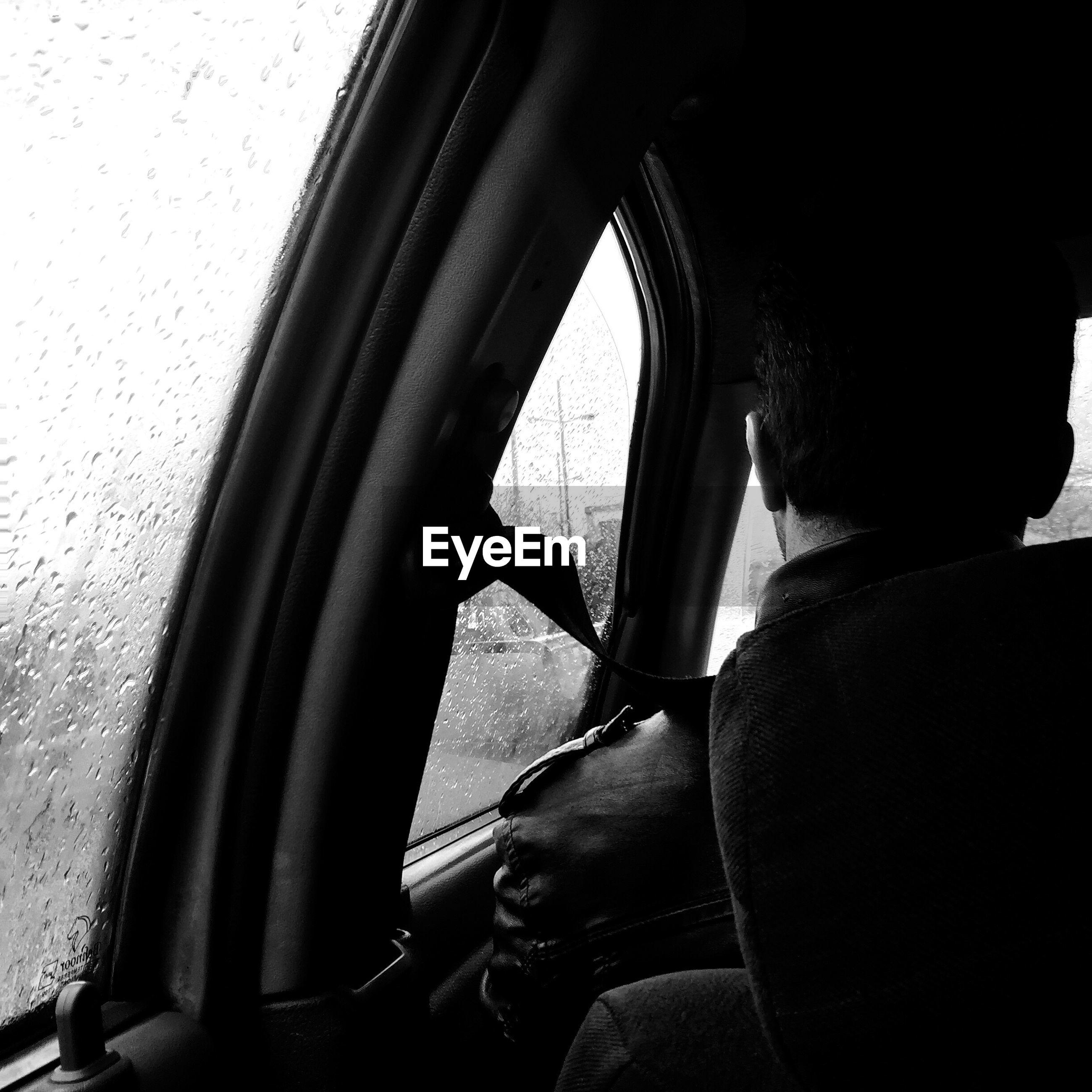 REFLECTION OF MAN SITTING IN CAR WINDOW