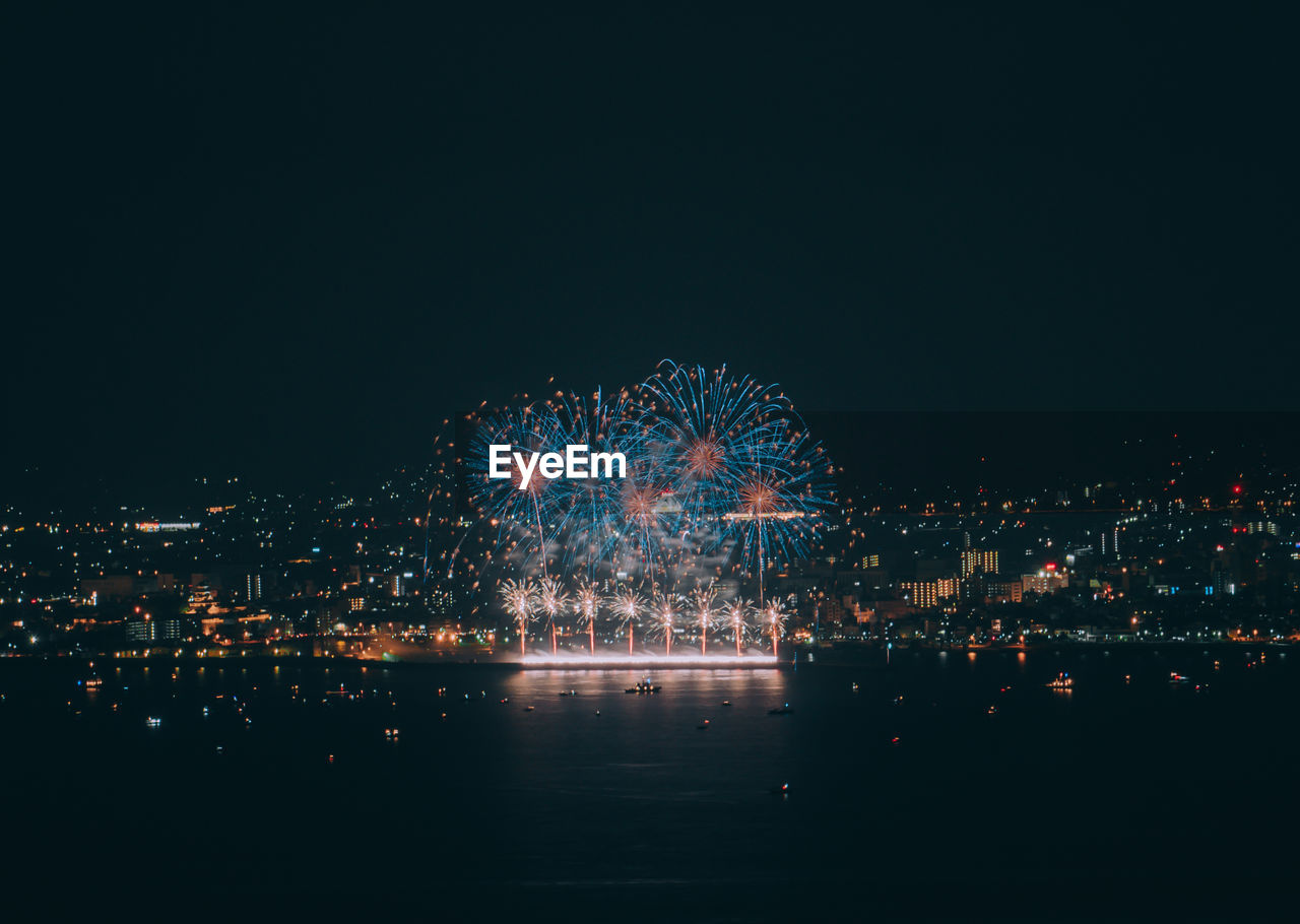 illuminated, night, building exterior, architecture, city, built structure, sky, celebration, copy space, cityscape, arts culture and entertainment, firework, glowing, nature, no people, firework display, event, exploding, light, clear sky, outdoors, firework - man made object