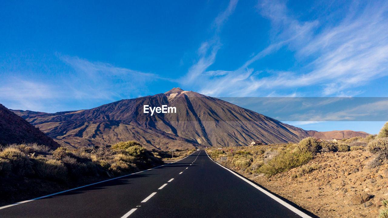 Empty Road Leading Towards Mountain Against Sky