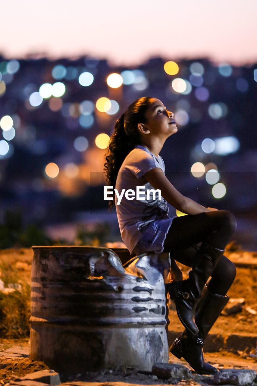 Side View Of Girl Sitting Damaged Metallic Barrel At Night
