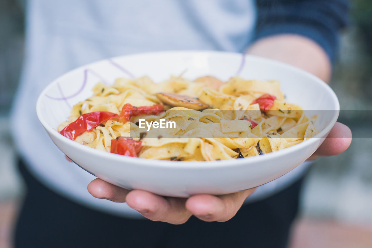 Close-Up Of Hand Holding Pasta In Bowl