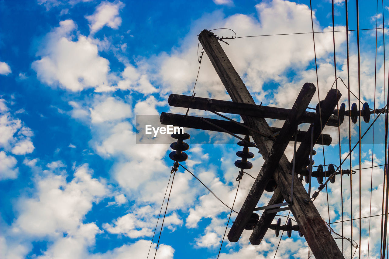 cloud - sky, sky, low angle view, blue, day, nature, no people, outdoors, metal, connection, fuel and power generation, built structure, architecture, wood - material, machinery, technology, tall - high, tower, sunlight, art and craft, power supply
