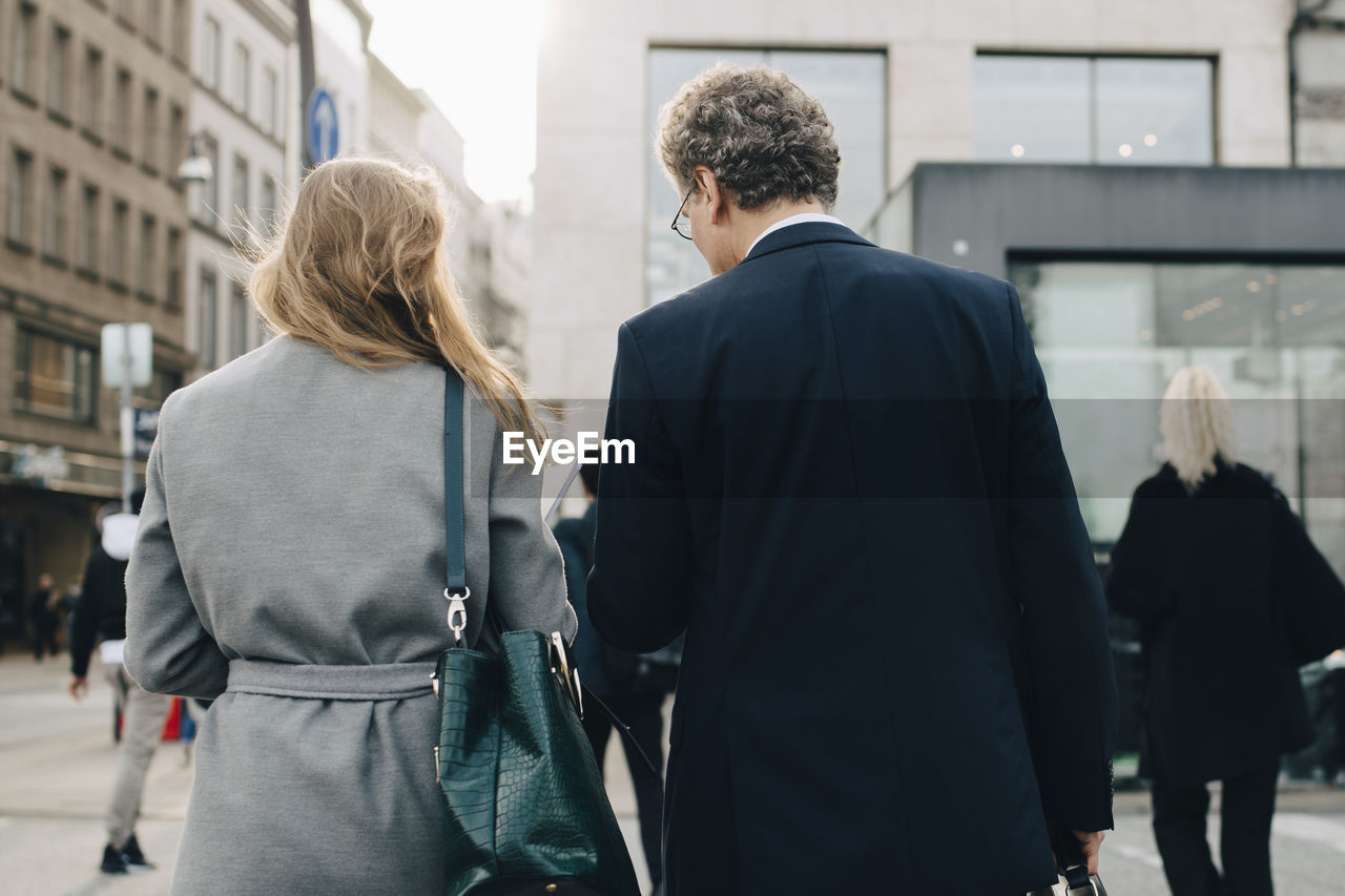 REAR VIEW OF COUPLE WALKING IN CITY