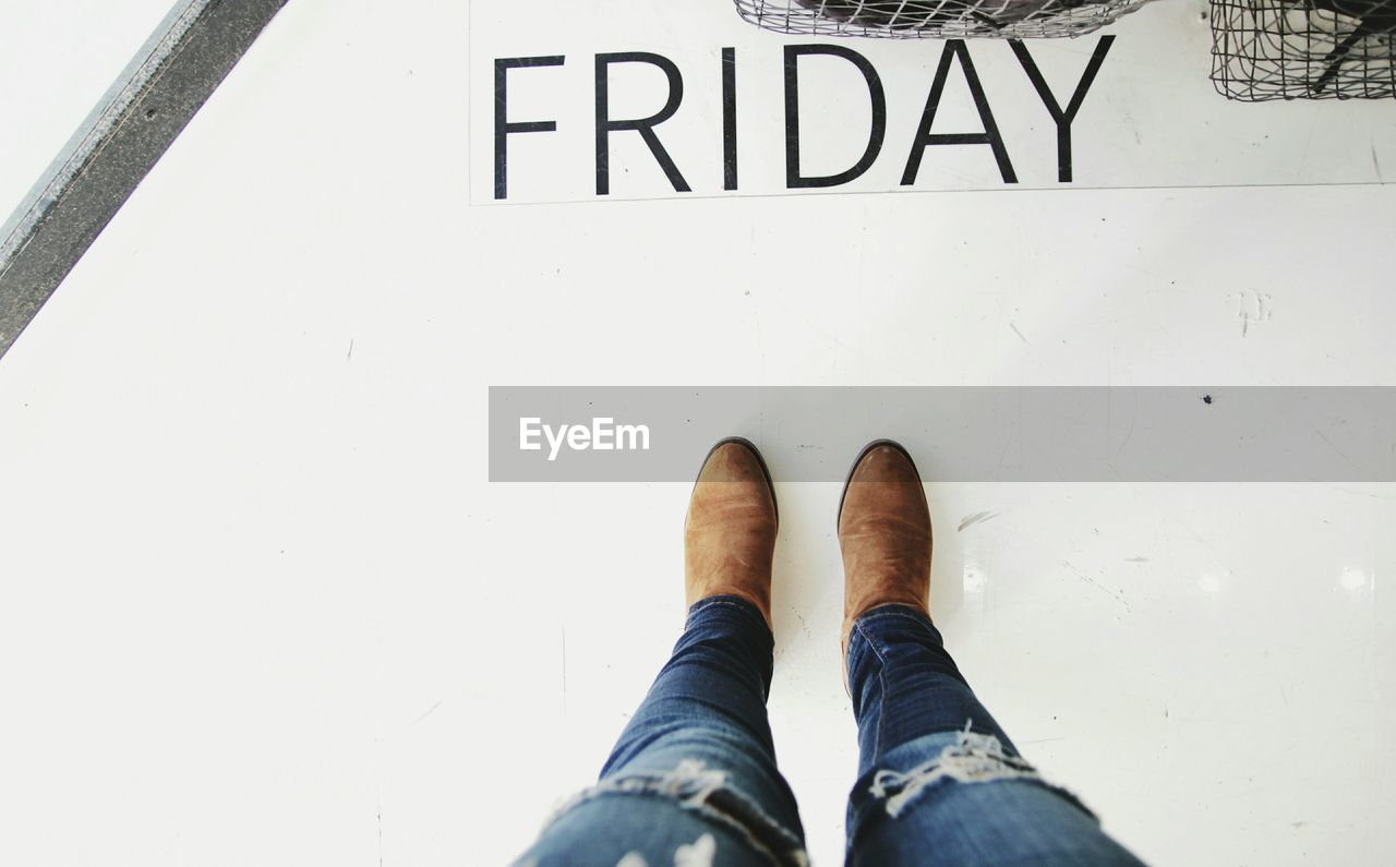 Low Section Of Person Standing On Floor With Friday Text