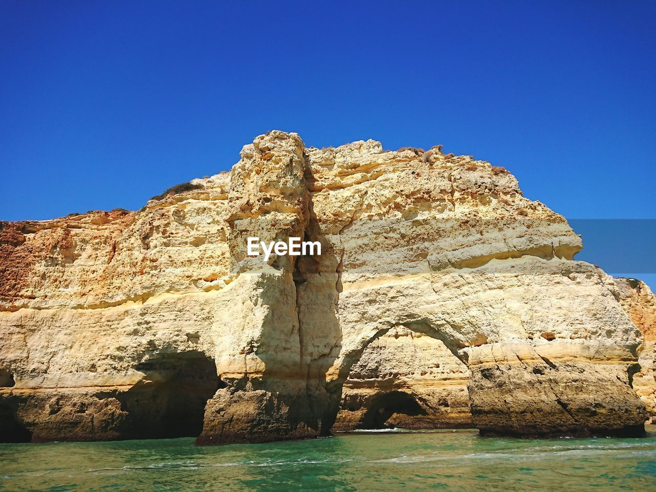 ROCK FORMATION BY SEA AGAINST CLEAR SKY