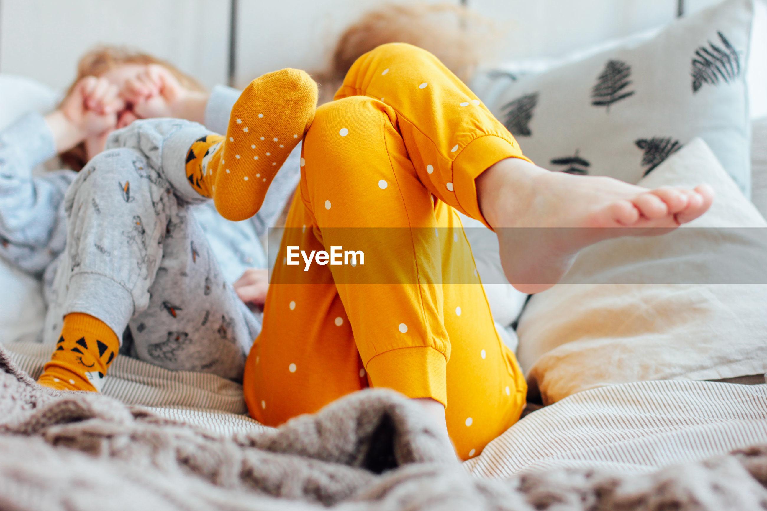 Siblings sleeping on bed at home