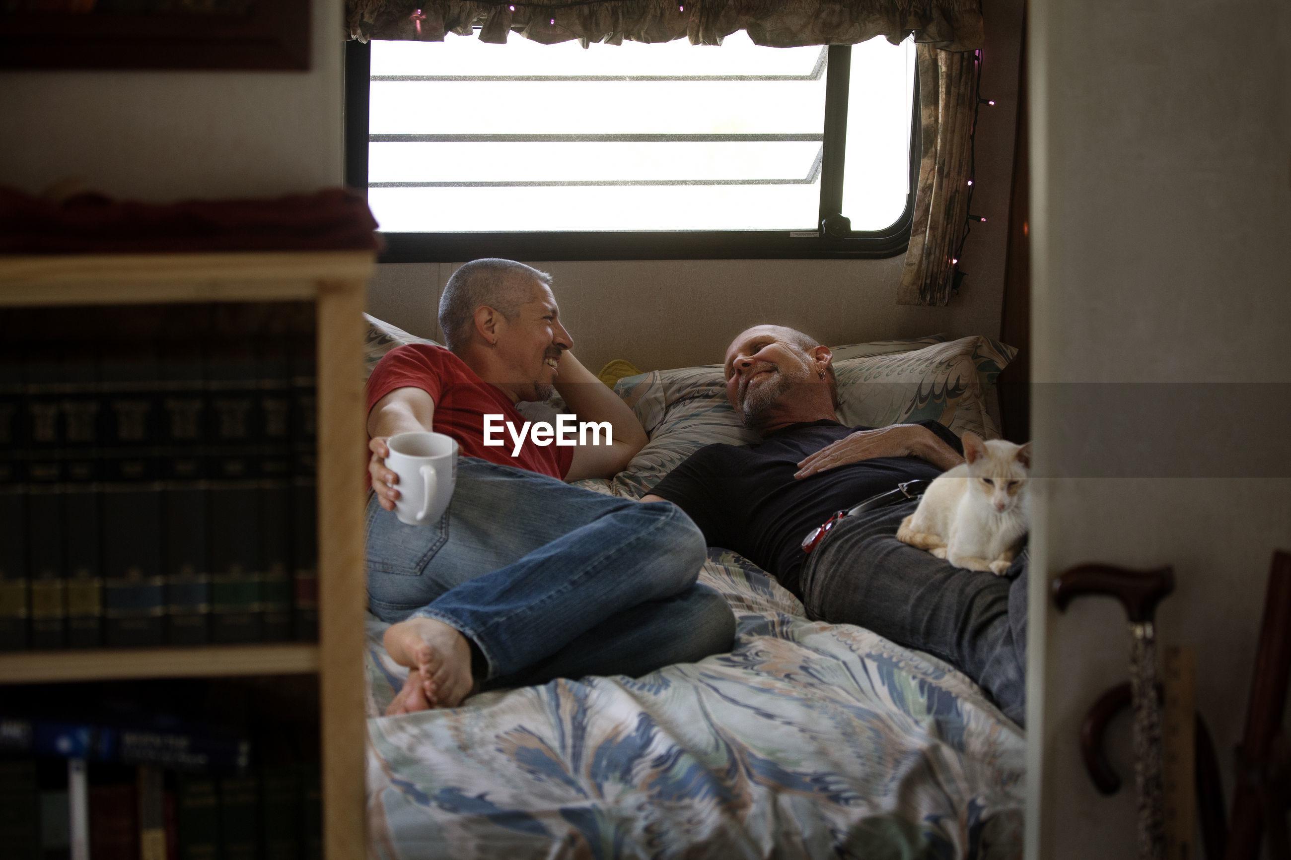 Happy gay couple sleeping on bed in camper van
