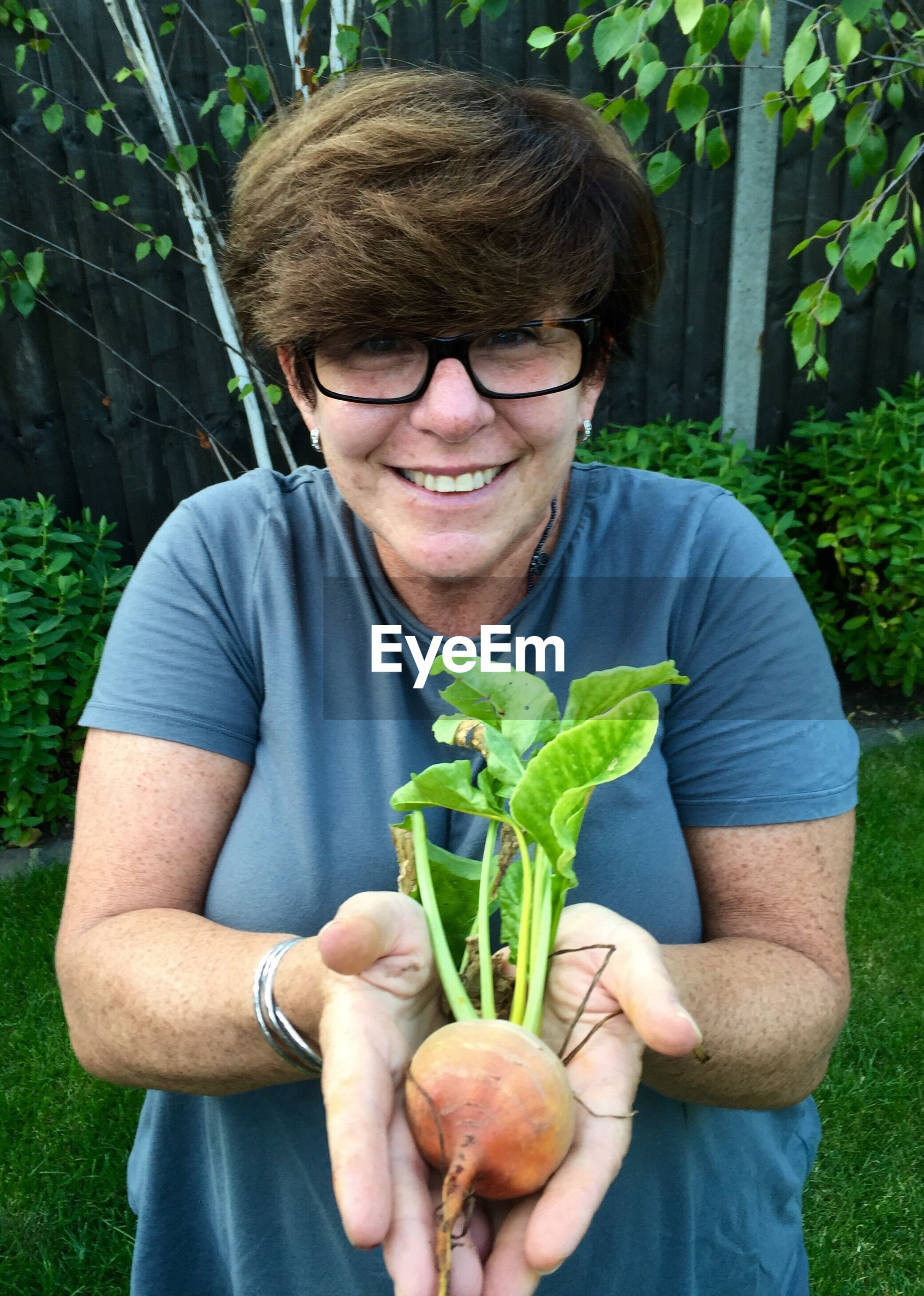 Portrait of smiling woman holding root vegetable at yard