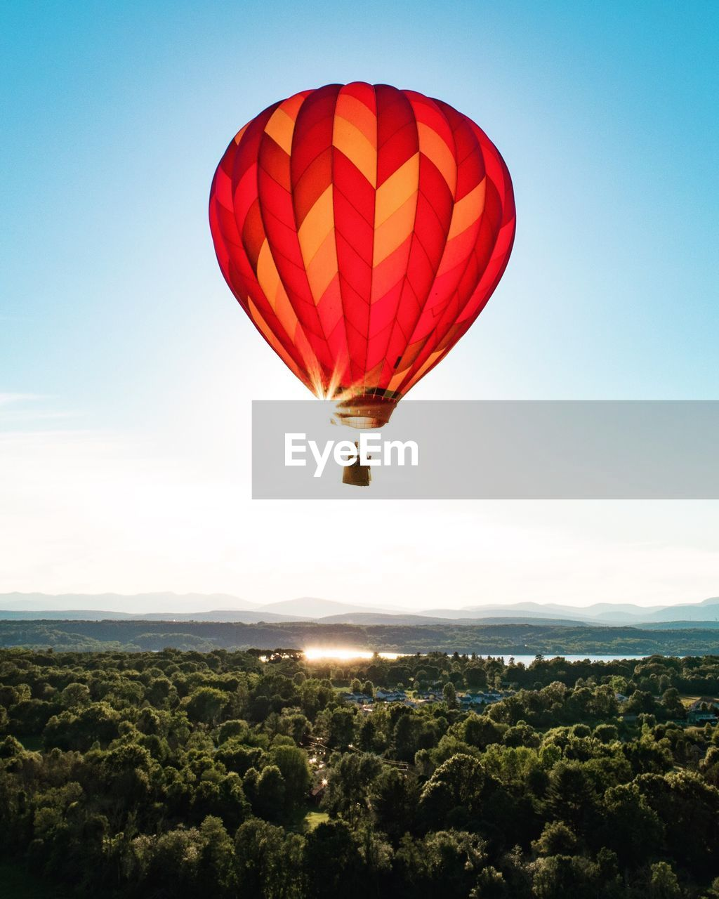 Red hot air balloon flying over landscape against clear sky
